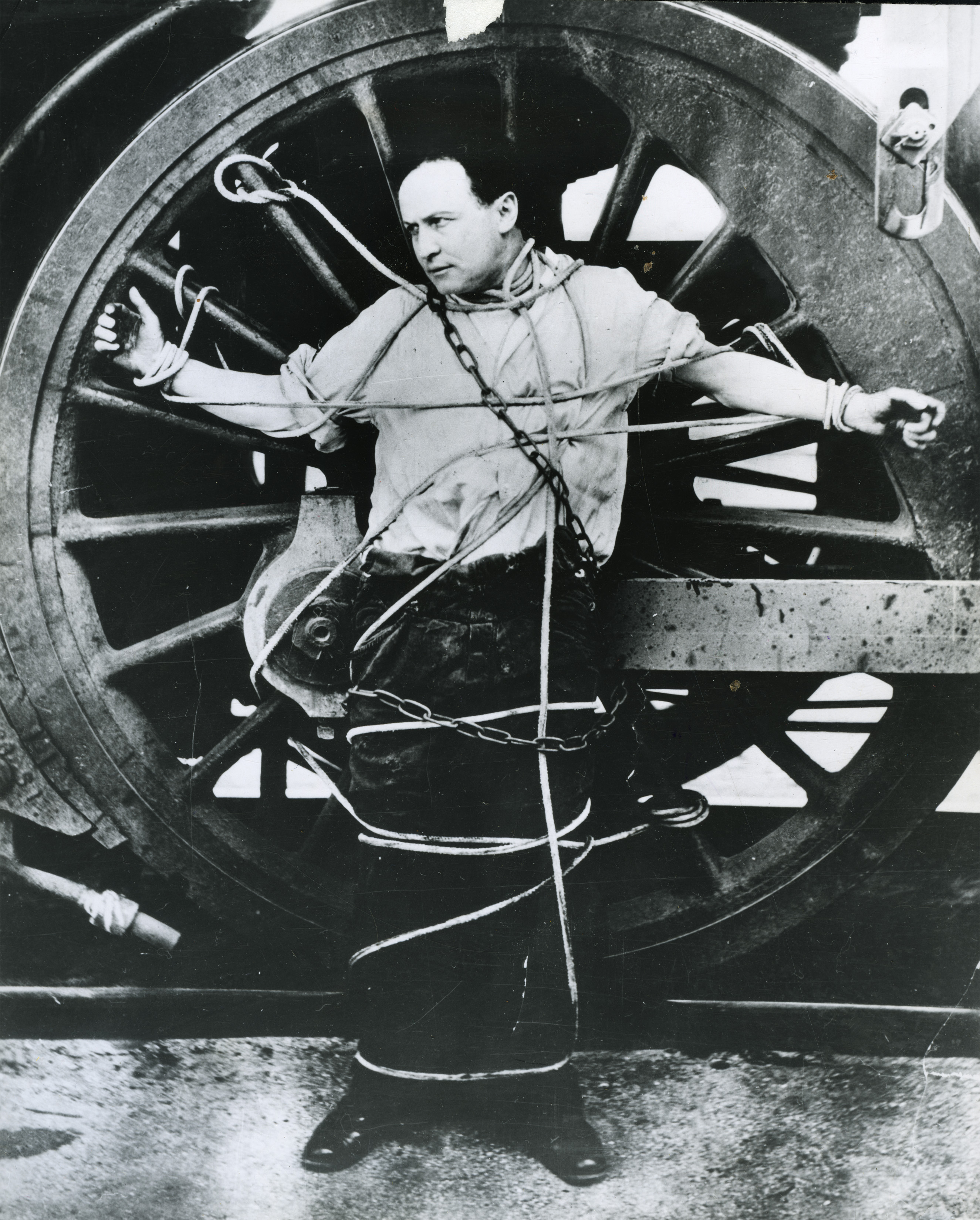 Houdini chains himself to a locomotive wheel for an escape attempt.