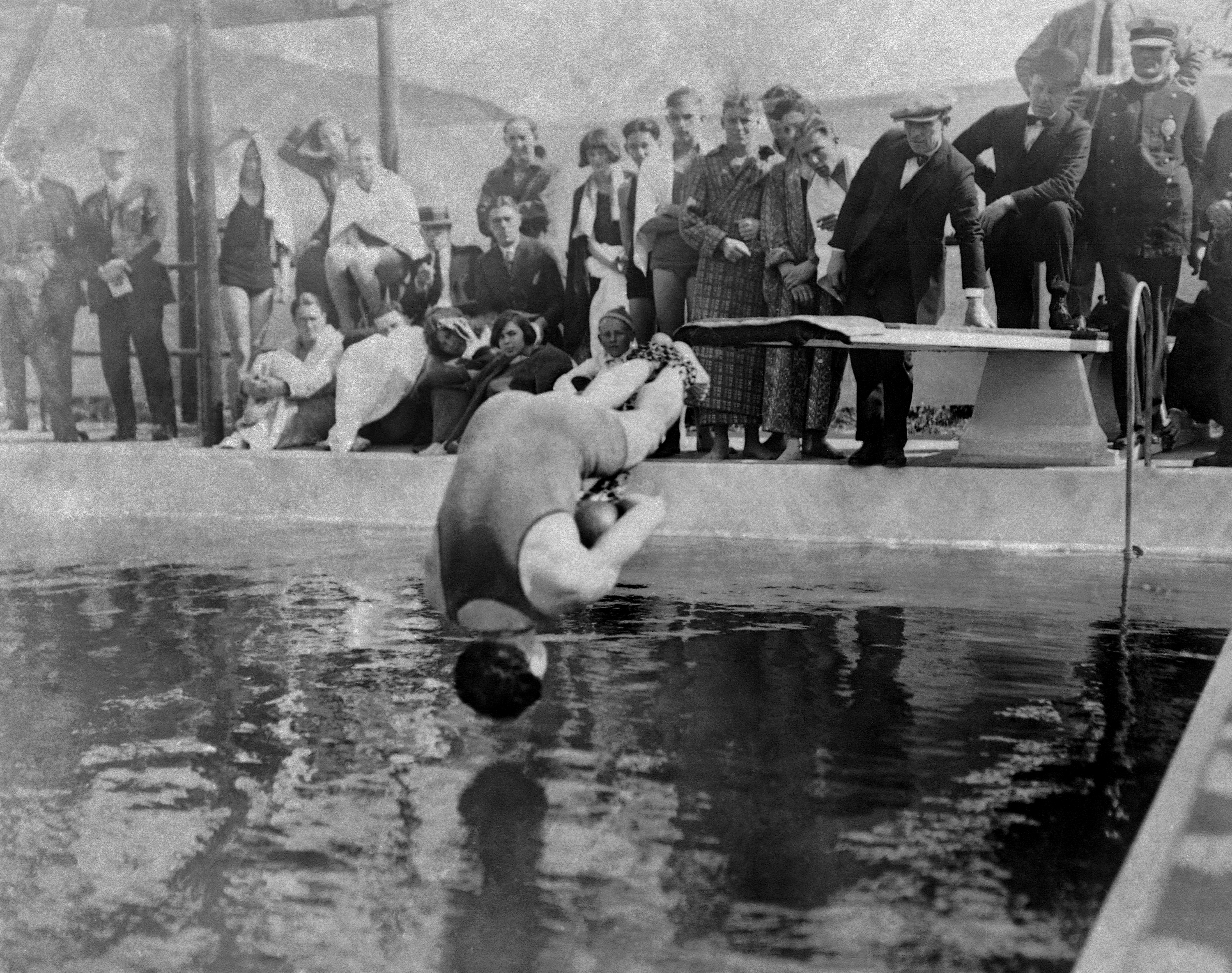 Houdini, handcuffed, and with his feet bound in chains, dives into pool in Los Angeles, May 7, 1923.