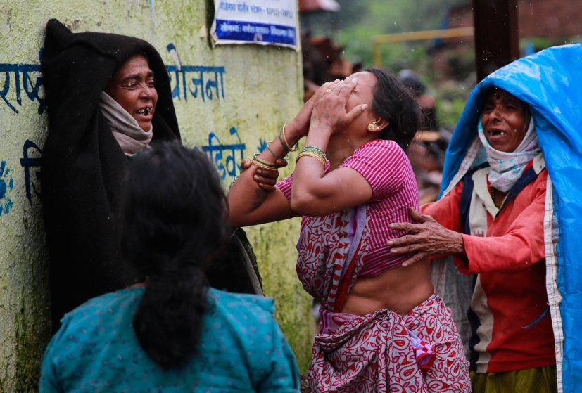 Relatives wail after seeing the body of a victim after a massive landslide in Malin village in Pune district of western Maharashtra state, India on July 31, 2014.