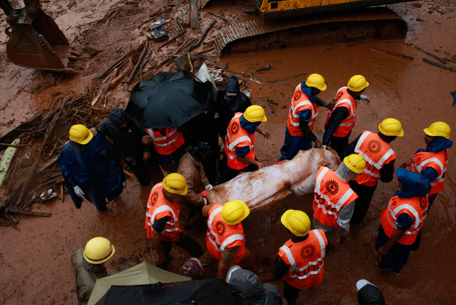 Rescue workers carry the body of a victim after a massive landslide in Malin village in Pune district of western Maharashtra state, India on July 31, 2014. Two days of torrential rains triggered the landslide early Wednesday, killing more than two dozen people and trapping more than 150, authorities said.