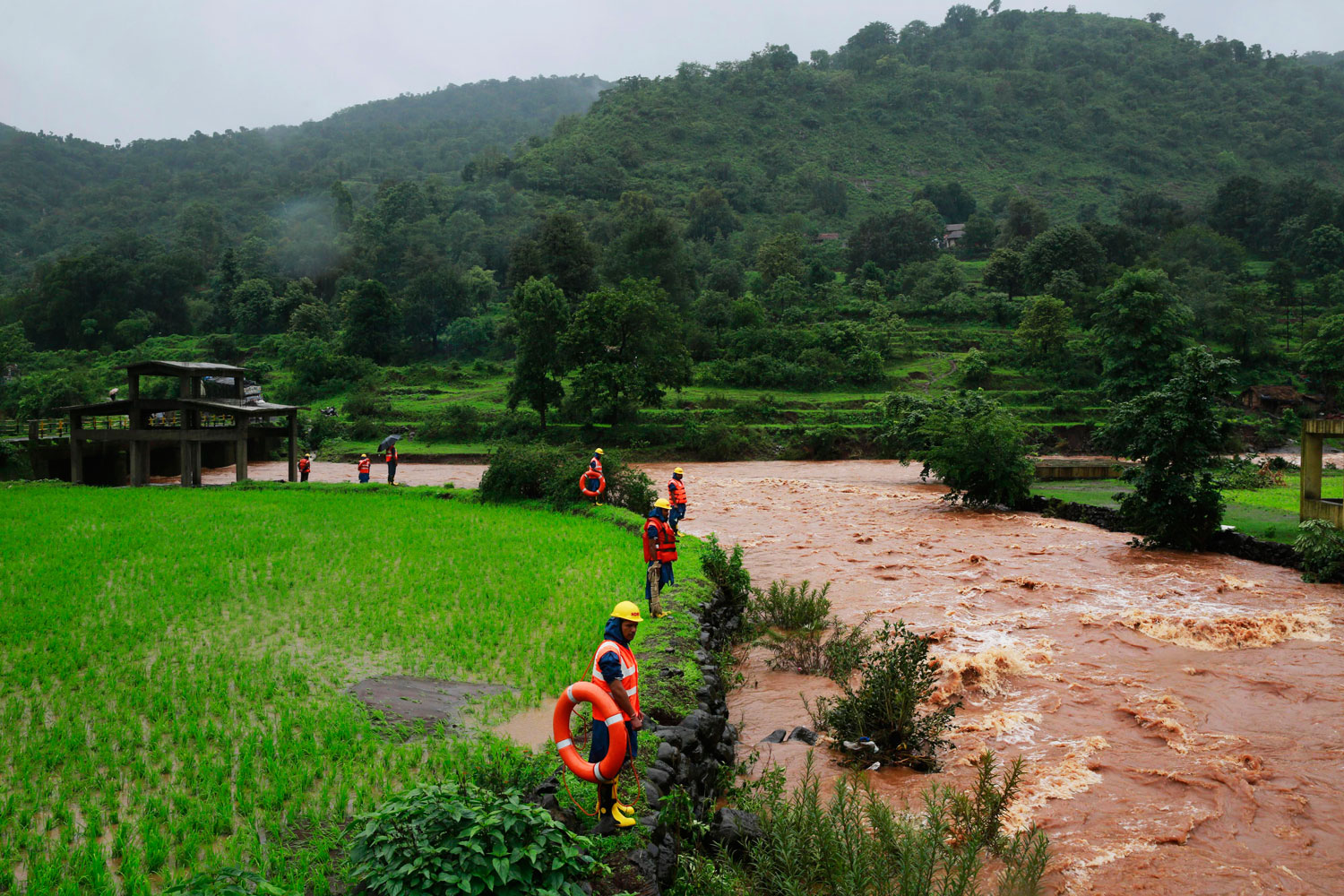 Rescue workers stand on the bank of a river as they look for bodies after a massive landslide in Malin village in Pune district of western Maharashtra state, India on July 31, 2014.