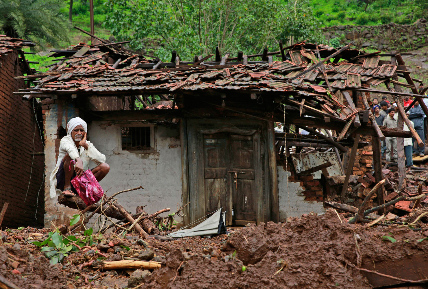 A villager watches a rescue operation sitting by his damaged house at the site of a landslide in Malin village, in the western Indian state of Maharashtra on Aug. 1, 2014.