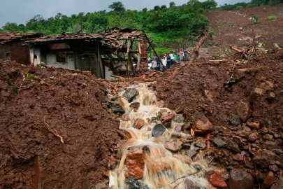 Villagers watch a rescue operation standing by mud and slush at the site of a landslide in Malin village, in the western Indian state of Maharashtra on Aug. 1, 2014.