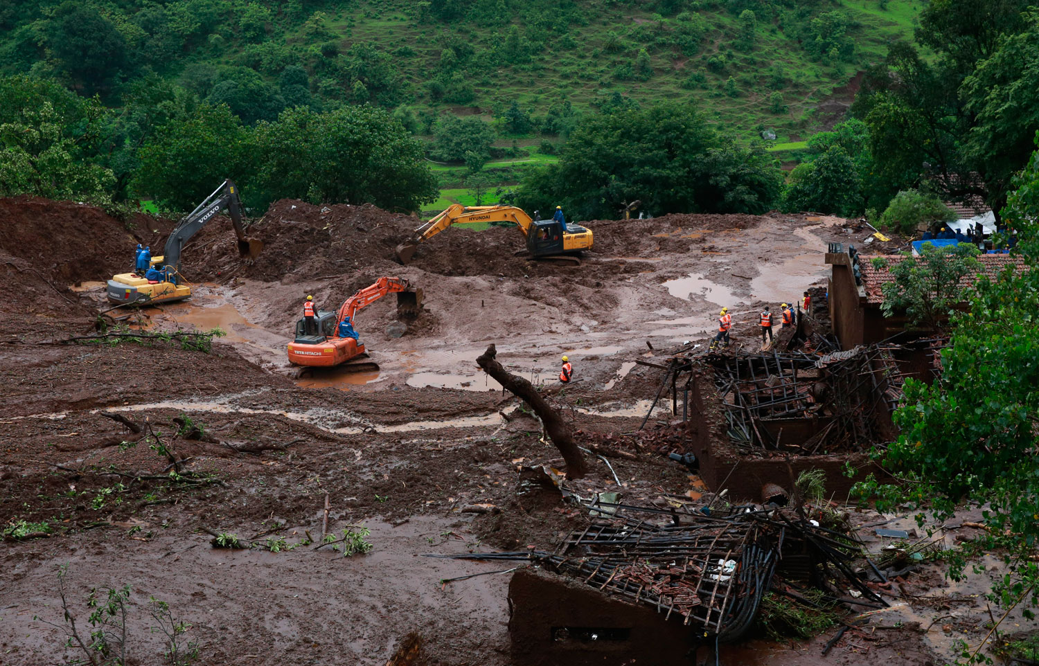 Earthmovers clear mud and slush at the site of a landslide in Malin village, in the western Indian state of Maharashtra on Aug. 1, 2014.