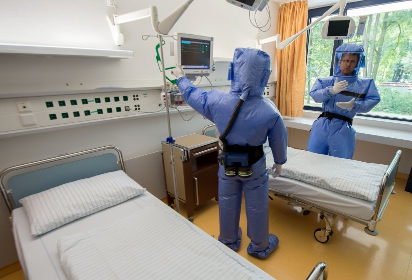 Infectious disease specialist Florian Steiner and quarantine office leader Thomas Klotzkowski wear protective clothing as they stand in a sick room during a demonstration of the proceedings at the ward of Berlin's Charite hospital on August 11, 2014.