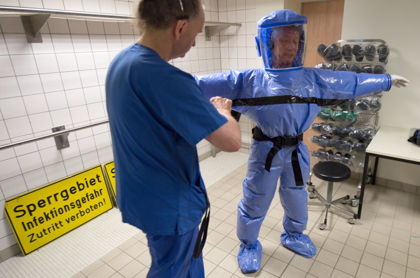Thomas Grosse helps quarantine office leader Thomas Klotzkowski to put on protective clothing during a demonstration of the proceedings at the quarantine office of Berlin's Charite hospital on August 11, 2014.