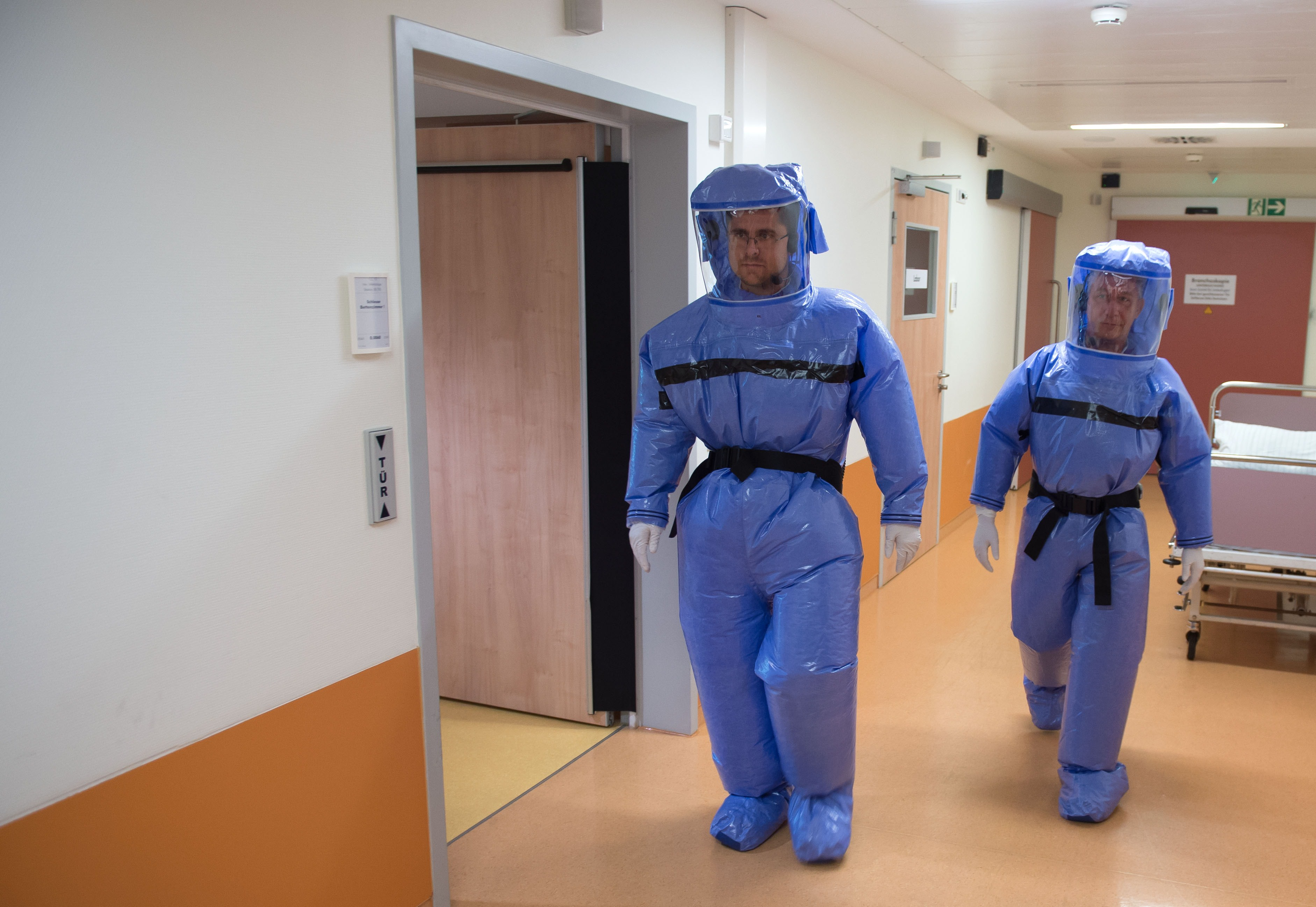 Infectious disease specialist Florian Steiner and quarantine office leader Thomas Klotzkowski wear protective clothing as they demonstrate the proceedings at the ward of Berlin's Charite hospital on August 11, 2014.