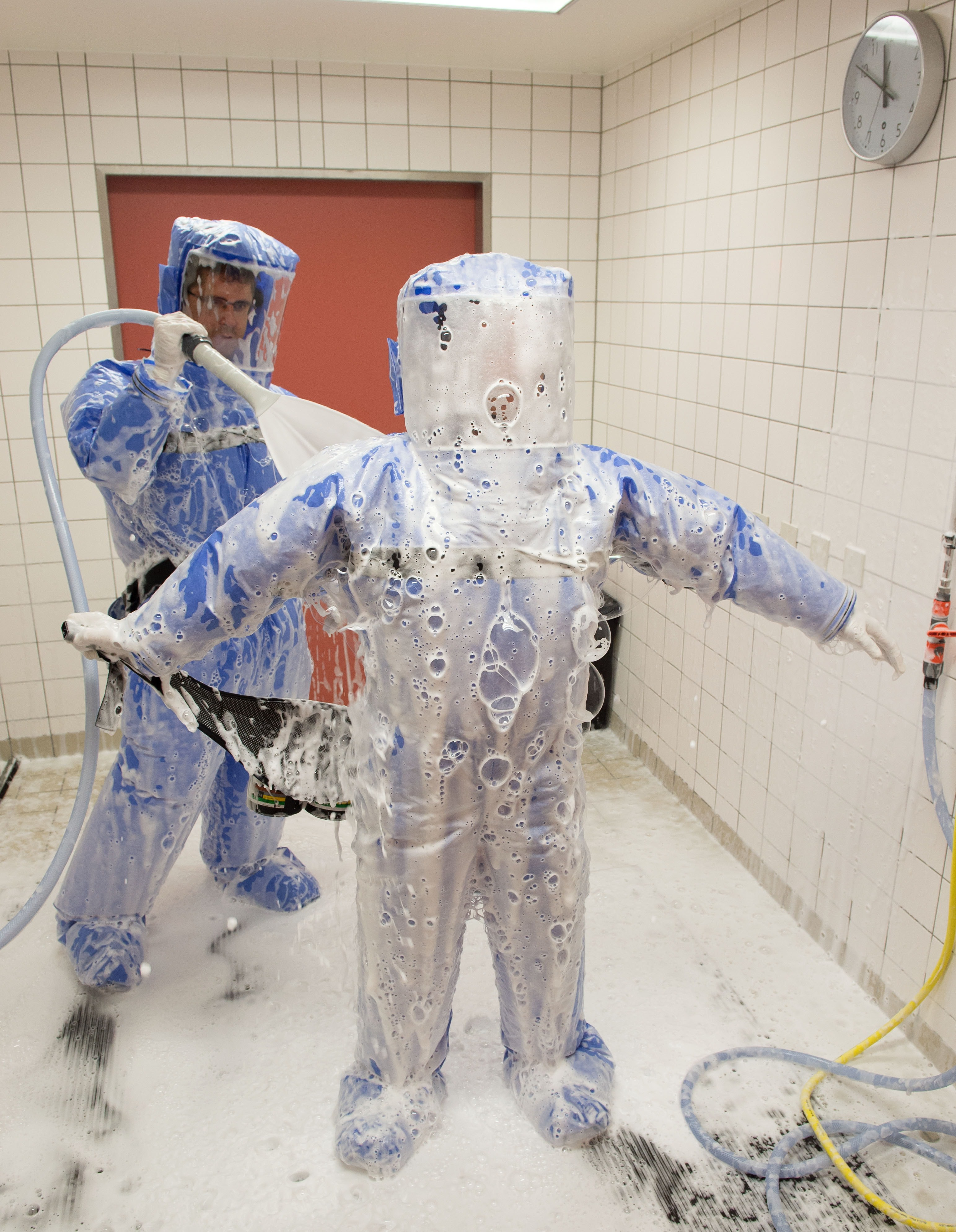 Infectious disease specialist Florian Steiner and quarantine office leader Thomas Klotzkowski disinfect themselves during a demonstration of the proceedings at the ward of Berlin's Charite hospital on August 11, 2014.