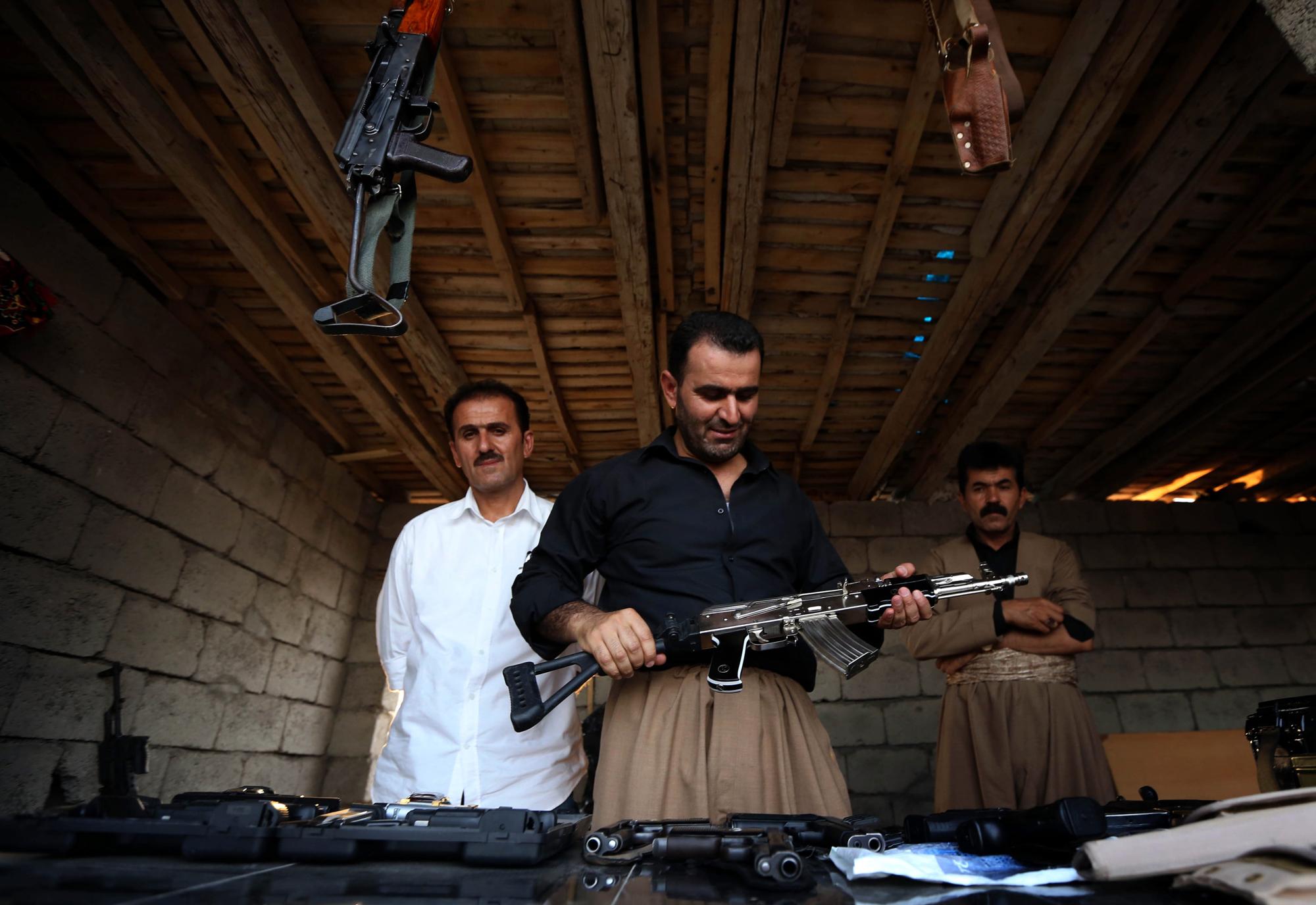 An Iraqi Kurd inspects a machine gun at an arms market in Erbil, the capital of the autonomous Kurdish region of northern Iraq on Aug. 17, 2014.