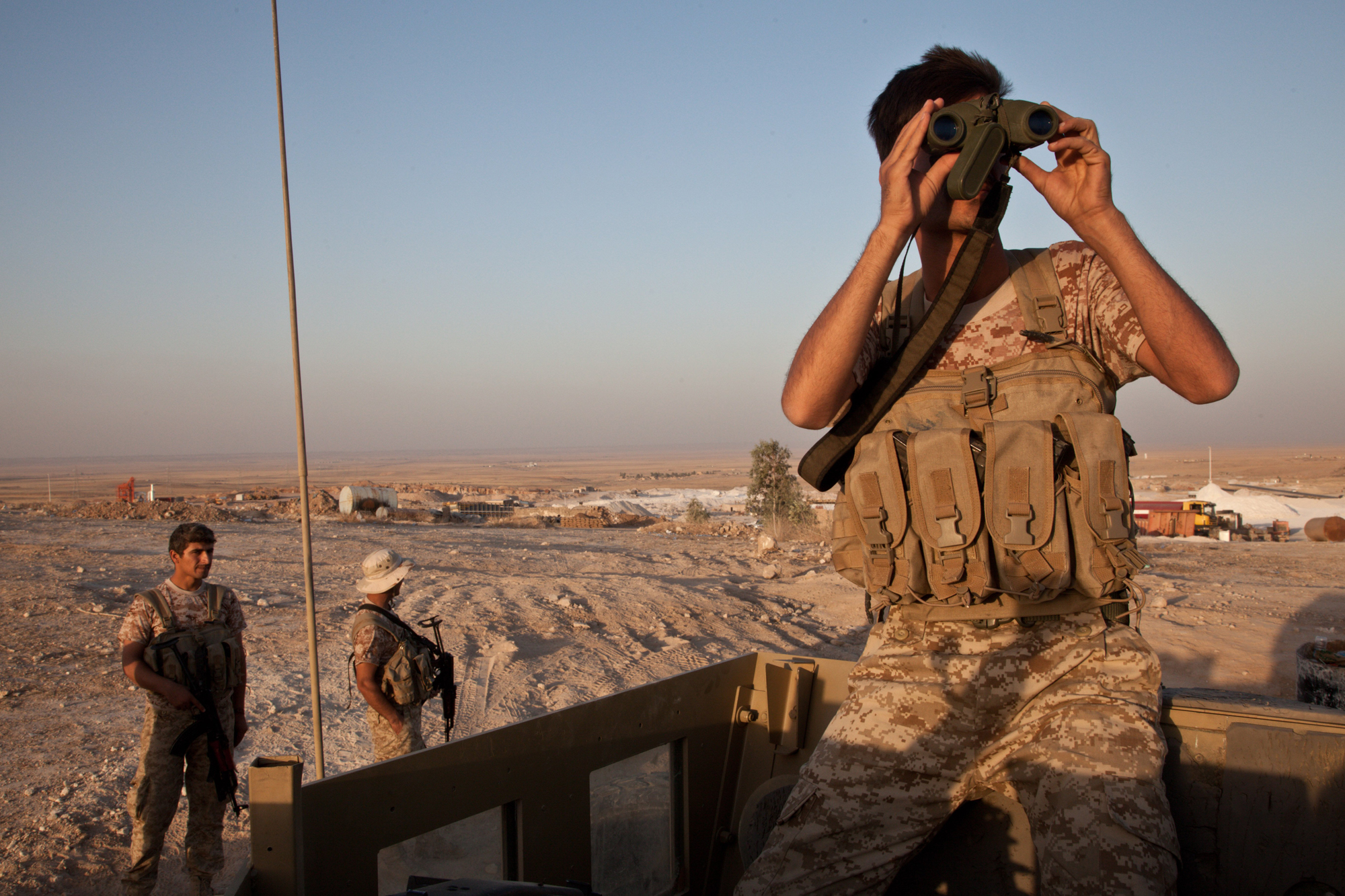 A Kurdish peshmerga soldier looks out over the town of Makhmour from defensive positions, Aug. 11, 2014.