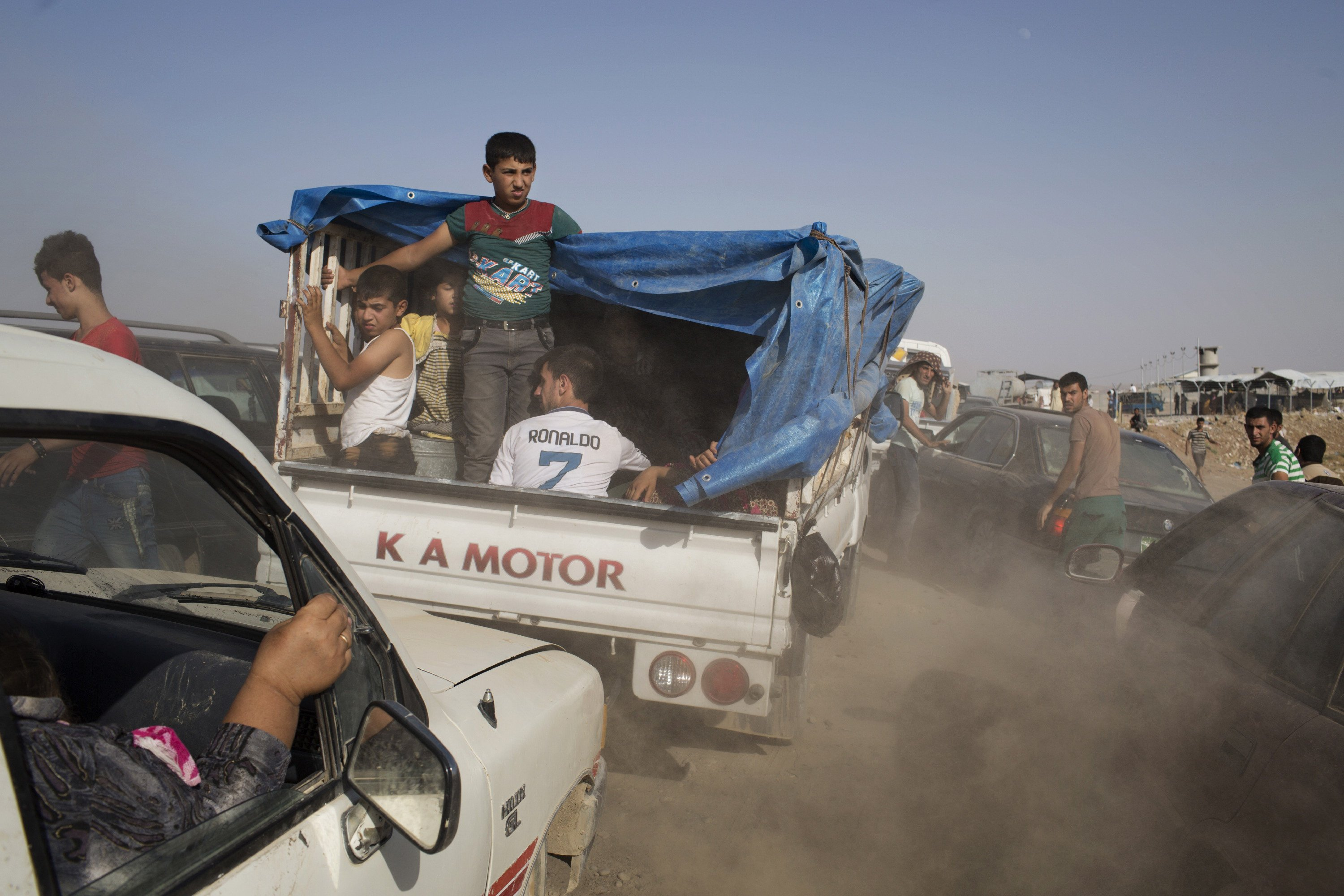 Iraqis arrive at a Kurdish peshmerga controlled checkpoint between Irbil and Mosul after fleeing in fear of ISIS attacks, Aug. 6, 2014.
