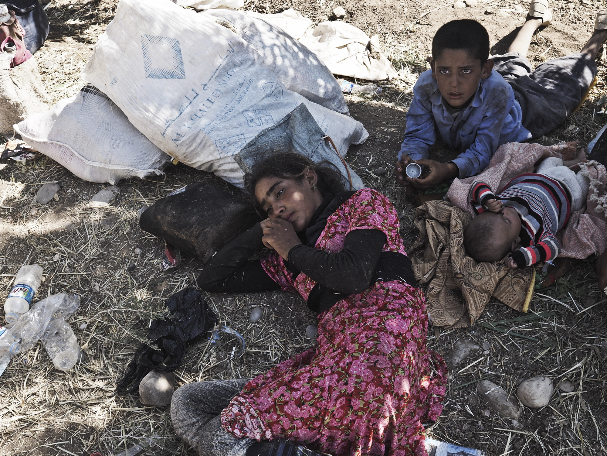 14-year-old Tawaf Ismail, a Yazidi girl from Sinjar, rests next to her brothers after arriving at the Fishkhabur border crossing between Iraq's Dohuk Province and Syria, Aug. 10, 2014.