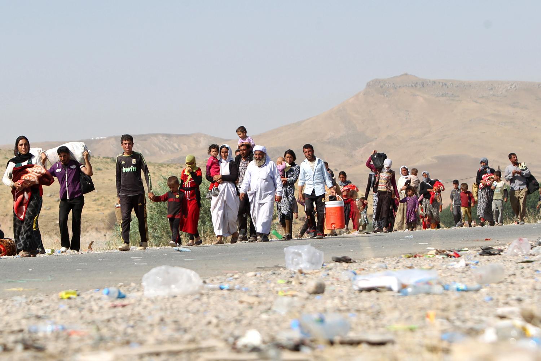 Displaced Iraqi Yezidi families cross the Iraqi-Syrian border in northern Iraq on Aug. 13, 2014
