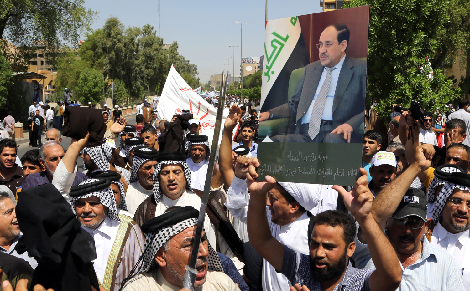 Iraqis chant pro-government slogans and wave national flags to show support for Prime Minister Nouri al-Maliki, during a demonstration in Baghdad, Iraq on August 9, 2014.