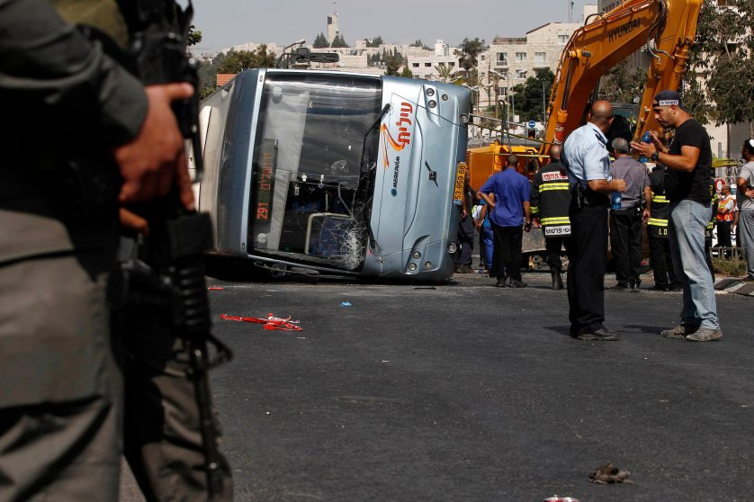 Israeli policemen stand next to an overturned bus at the scene of a suspected attack in Jerusalem, Aug. 4, 2014.