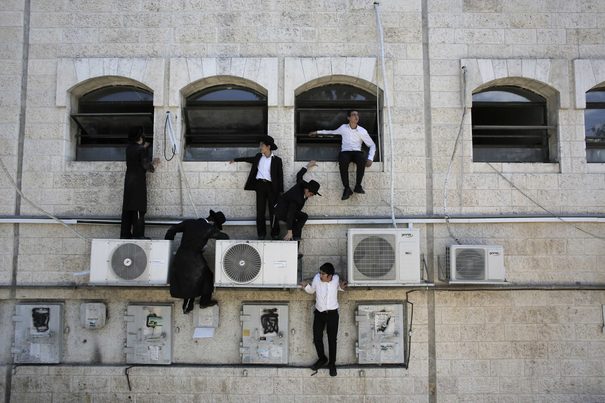 Ultra-Orthodox Jewish boys climb down a wall near the scene of a suspected attack in Jerusalem, Aug. 4, 2014.