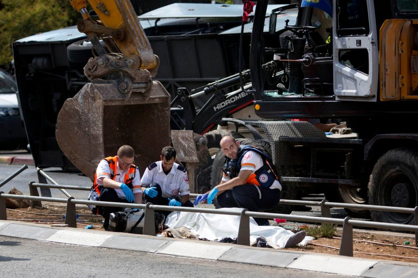 Israeli medics inspect a body at the scene of an attack in Jerusalem, Aug. 4, 2014.