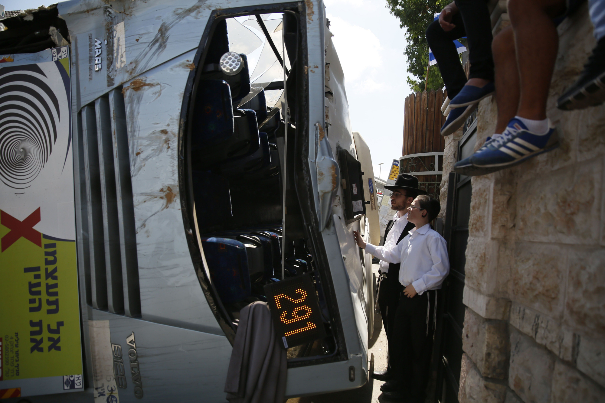 Onlookers inspect an overturned bus after a Palestinian man rammed an excavator into it, on Aug. 4, 2014 in Jerusalem, killing one person and lightly injuring five others.