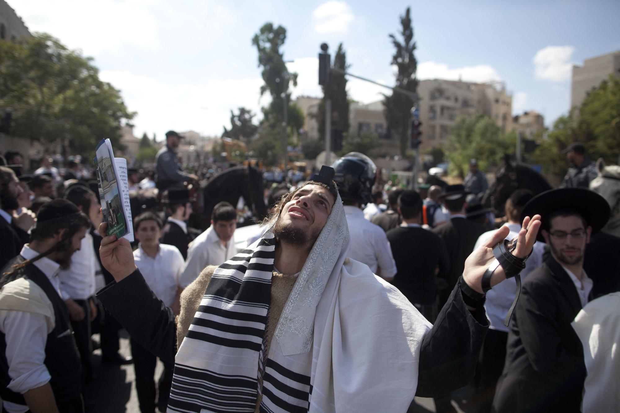 An Ultra Orthodox Jewish man prays near where a Palestinian man rammed an excavator into a bus on Aug. 4, 2014 in Jerusalem.