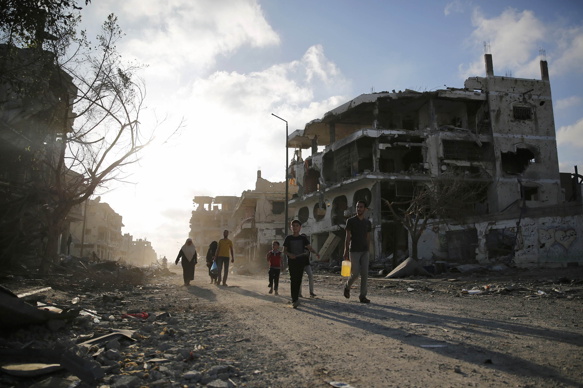 Palestinians walk amid the ruins of destroyed homes in the Shujayeh neighborhood, which witnesses said was heavily hit by Israeli shelling and air strikes during an Israeli offensive, east of Gaza City, Aug. 6, 2014.