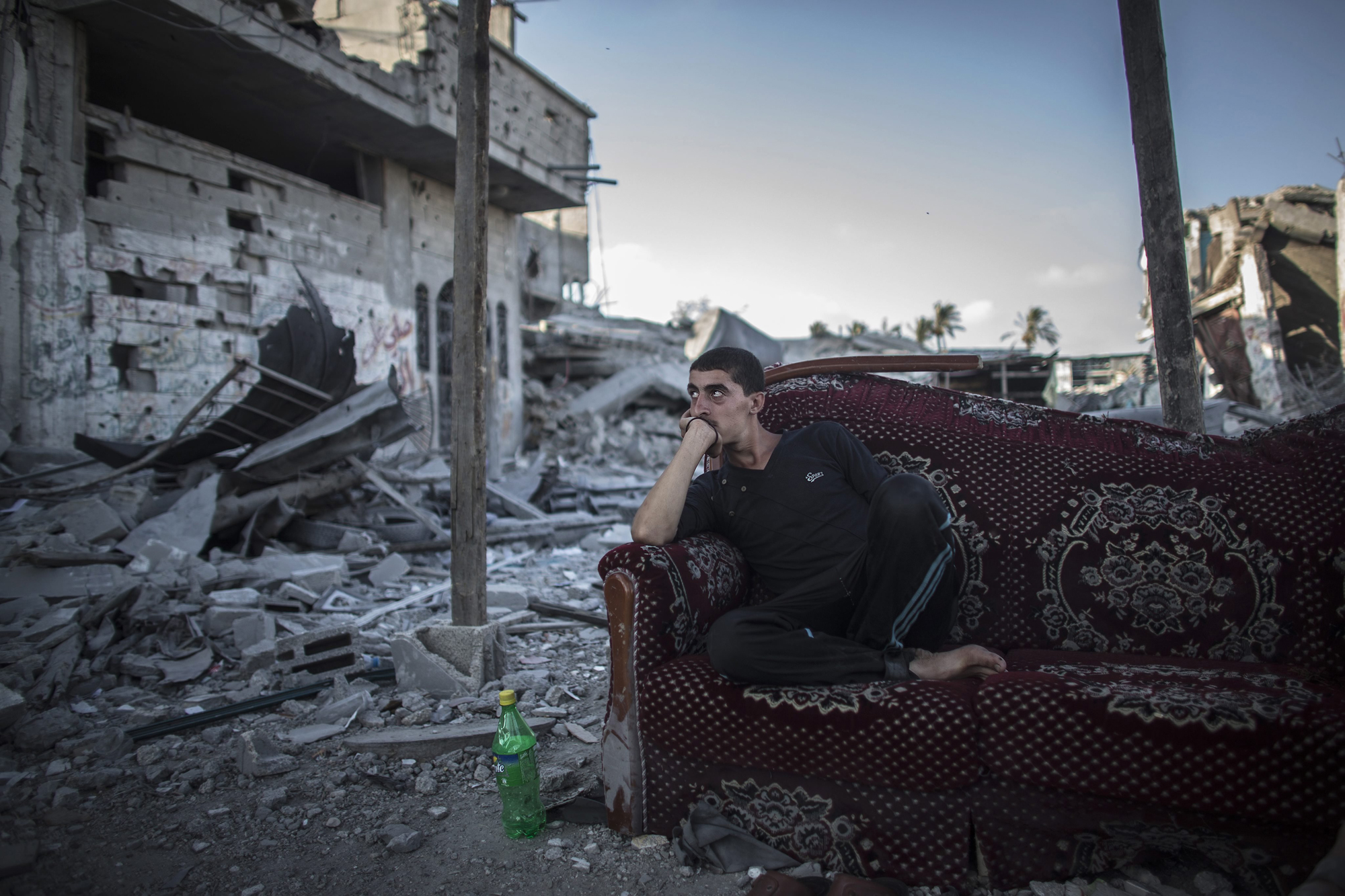 A Palestinian sits on a salvaged sofa outside his destroyed home in the Shujayeh neighborhood, east of Gaza City, Aug. 6, 2014.