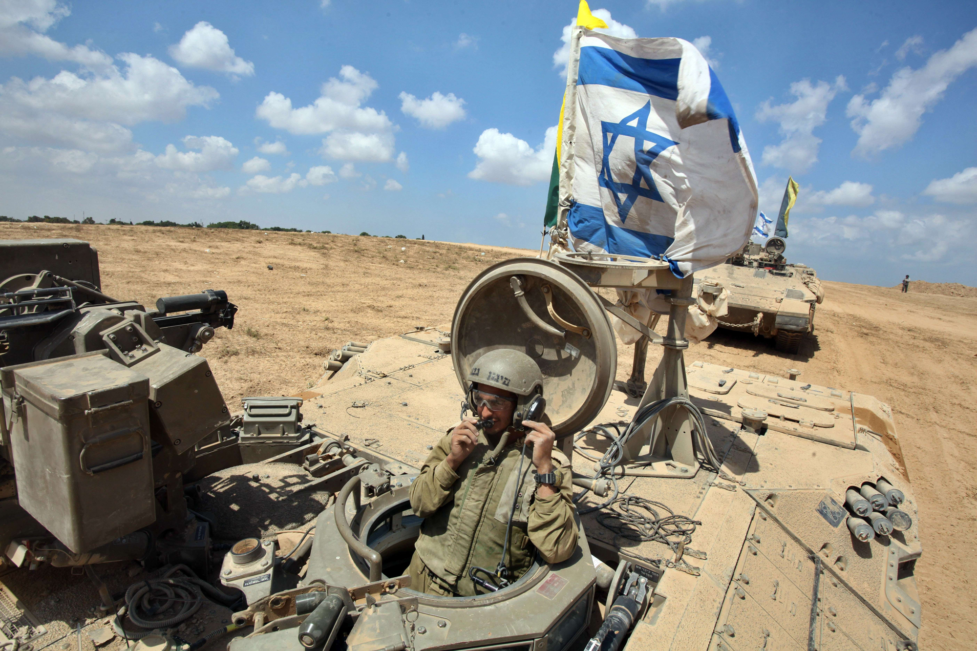 An Israeli soldier sits in an armored personnel carrier flying the Israeli flag as they return from the border between Israel and the Gaza Strip after pulling out of the Palestinian enclave on Aug. 4, 2014, as Israel has begun withdrawing some ground troops.