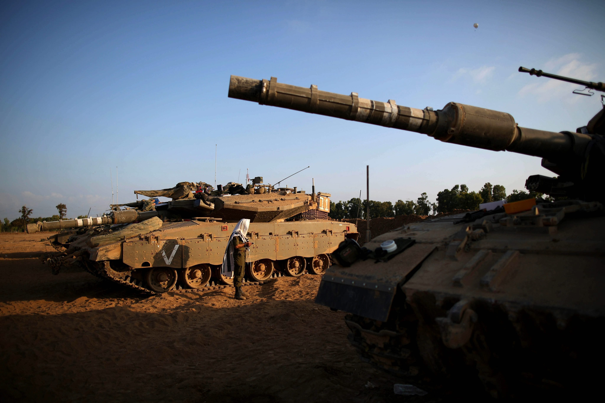 An Israeli soldier prays next to Merkava tanks at an unspecified location near the Israeli border with the Gaza Strip, Aug. 6, 2014.