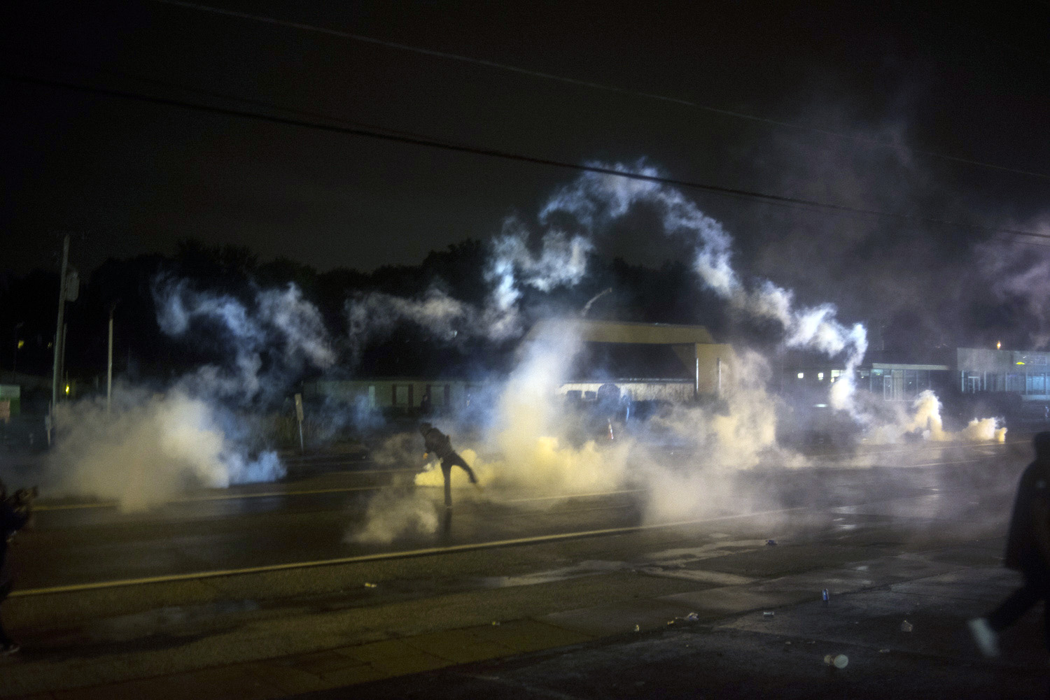 Protestors throw canisters                                    in Ferguson, Mo. on August 18, 2014.