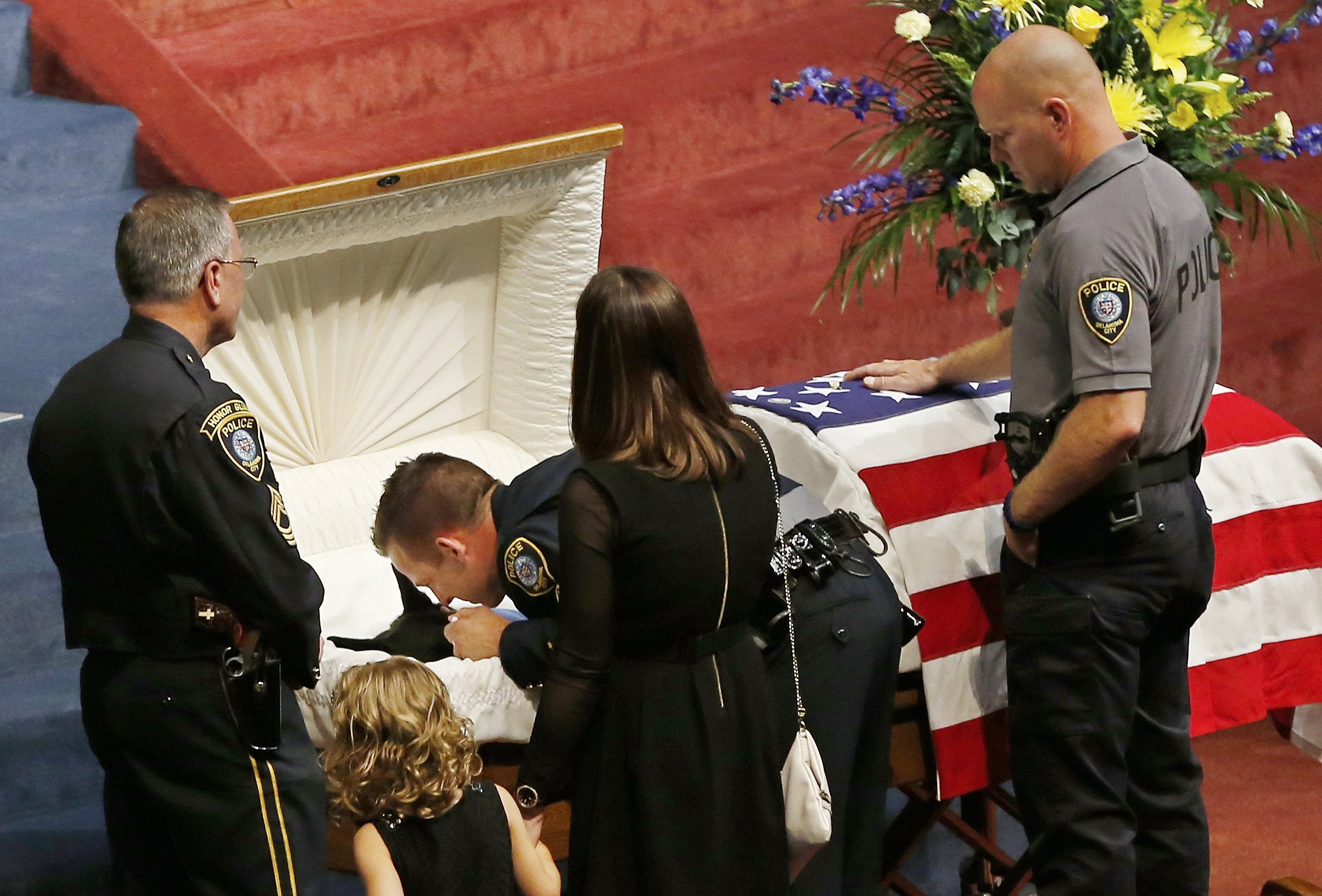 Oklahoma City police officer Sgt. Ryan Stark, center, leans over the casket of his canine partner, K-9 Kye, following funeral services for the dog in Oklahoma City, on Aug. 28, 2014.