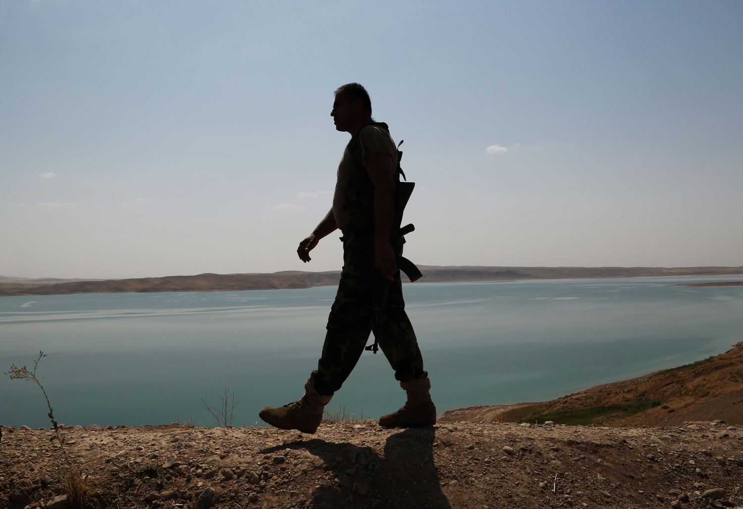 A Kurdish peshmerga fighter patrols near the Mosul Dam at the town of Chamibarakat outside Mosul, Iraq on Sunday, Aug. 17, 2014.