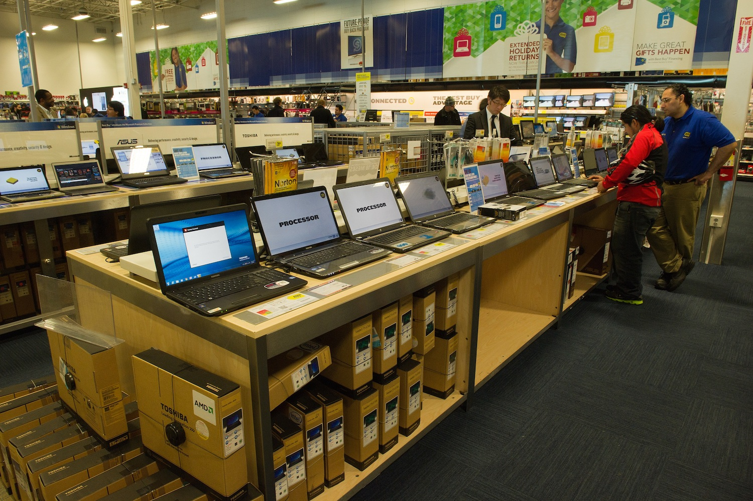 Customers look at laptop computers at a Best Buy store.