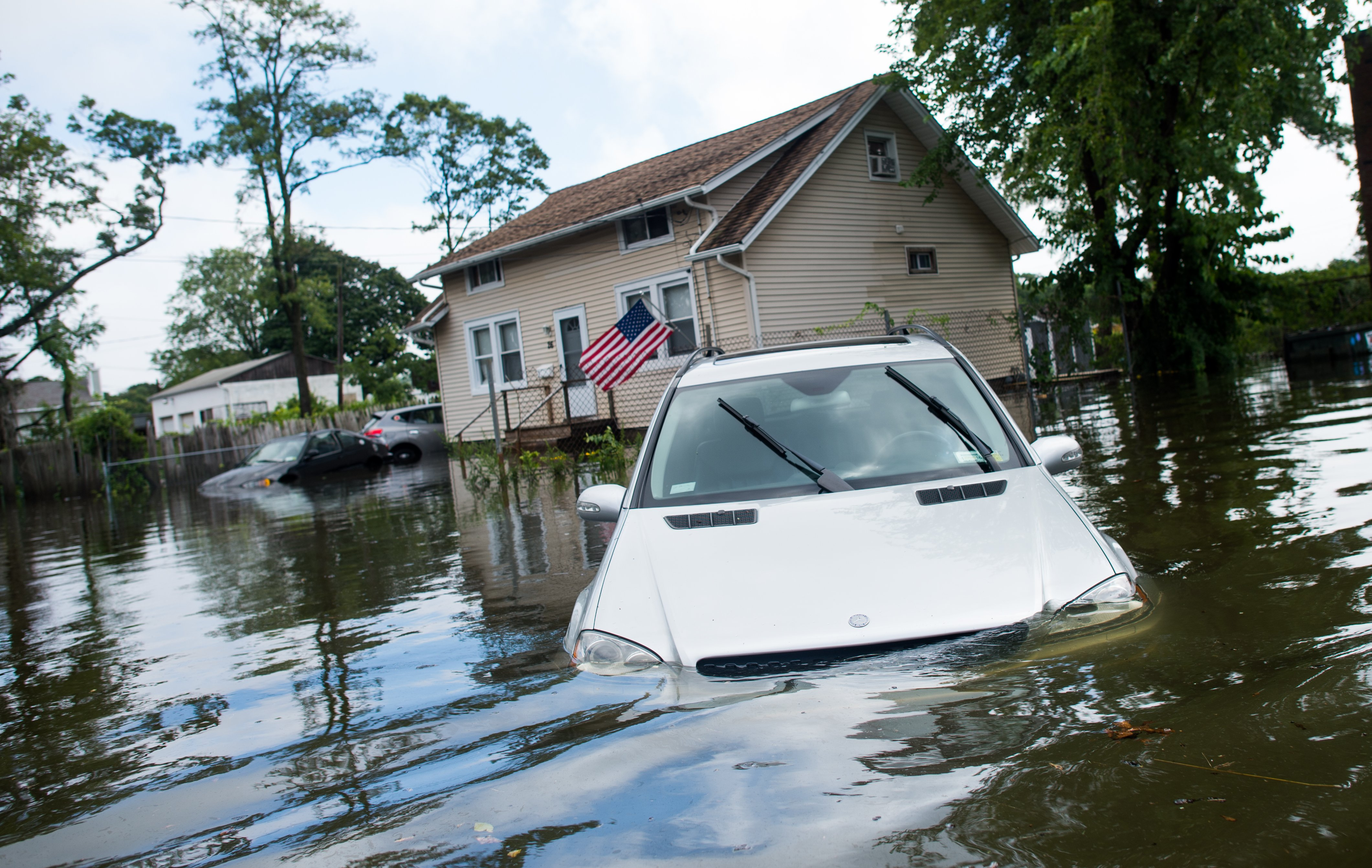 A car is abandoned on a flooded Reddington St. following heavy rains and flash flooding in Bayshore, N.Y. on Aug. 13, 2014.