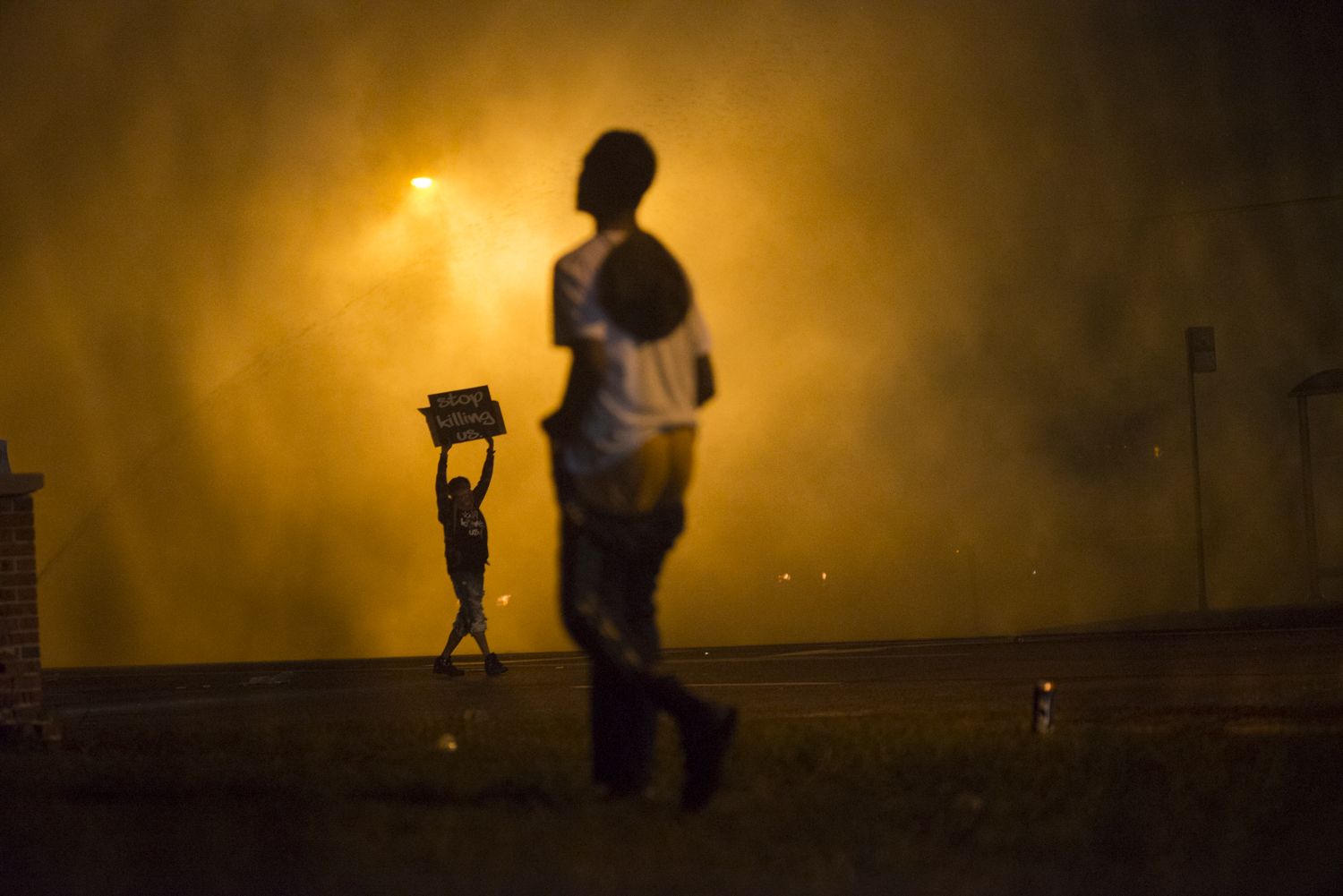 "A protestor holds a sign that reads ""stop killing us"" amid clouds of tear gas in Ferguson, Mo. on Aug. 17, 2014."