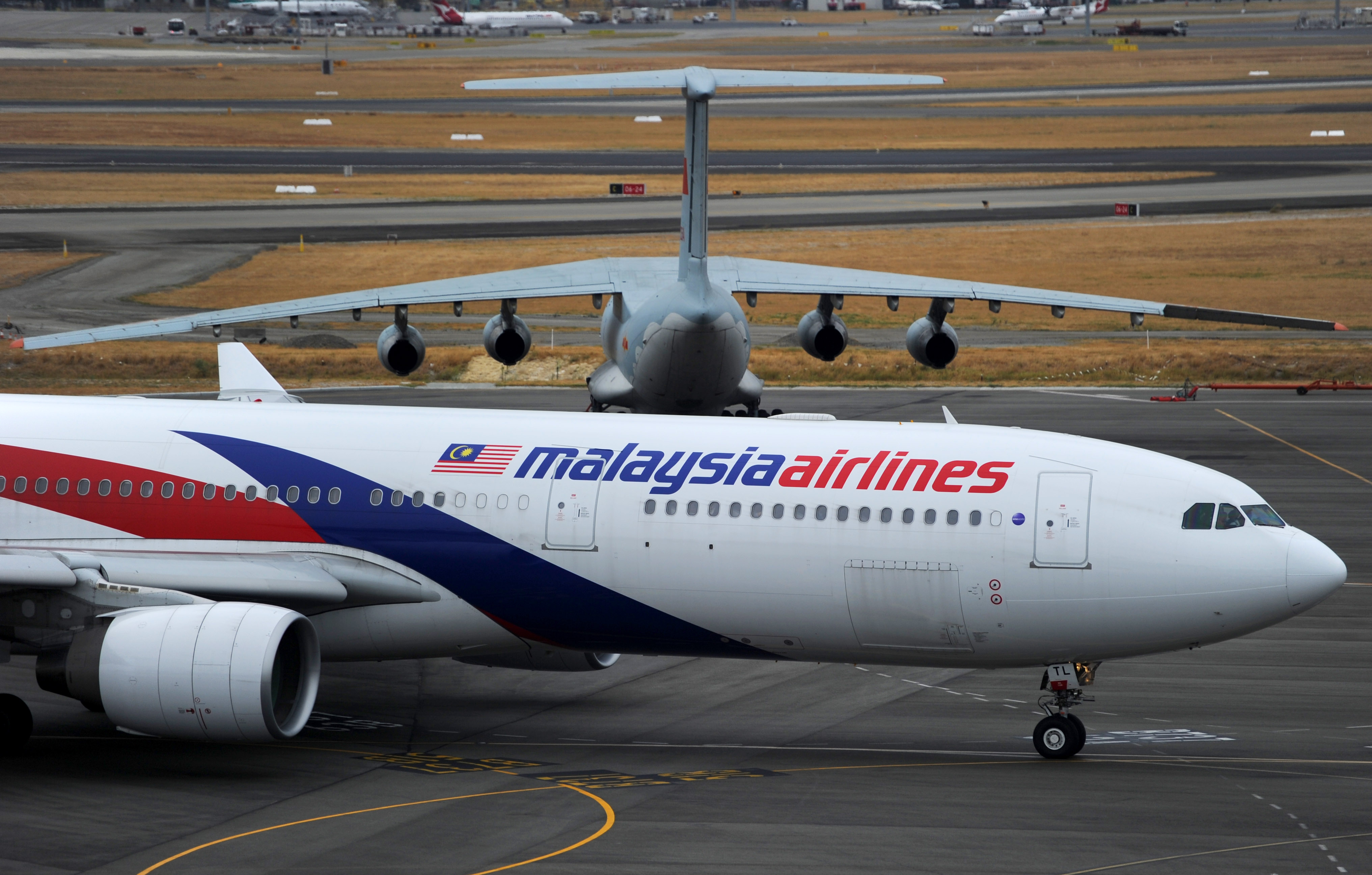 A Malaysia Airlines plane prepares to go out onto the runway and passes by a stationary Chinese Ilyushin 76 aircraft (top) at Perth International Airport on March 25, 2014 in Perth, Australia.