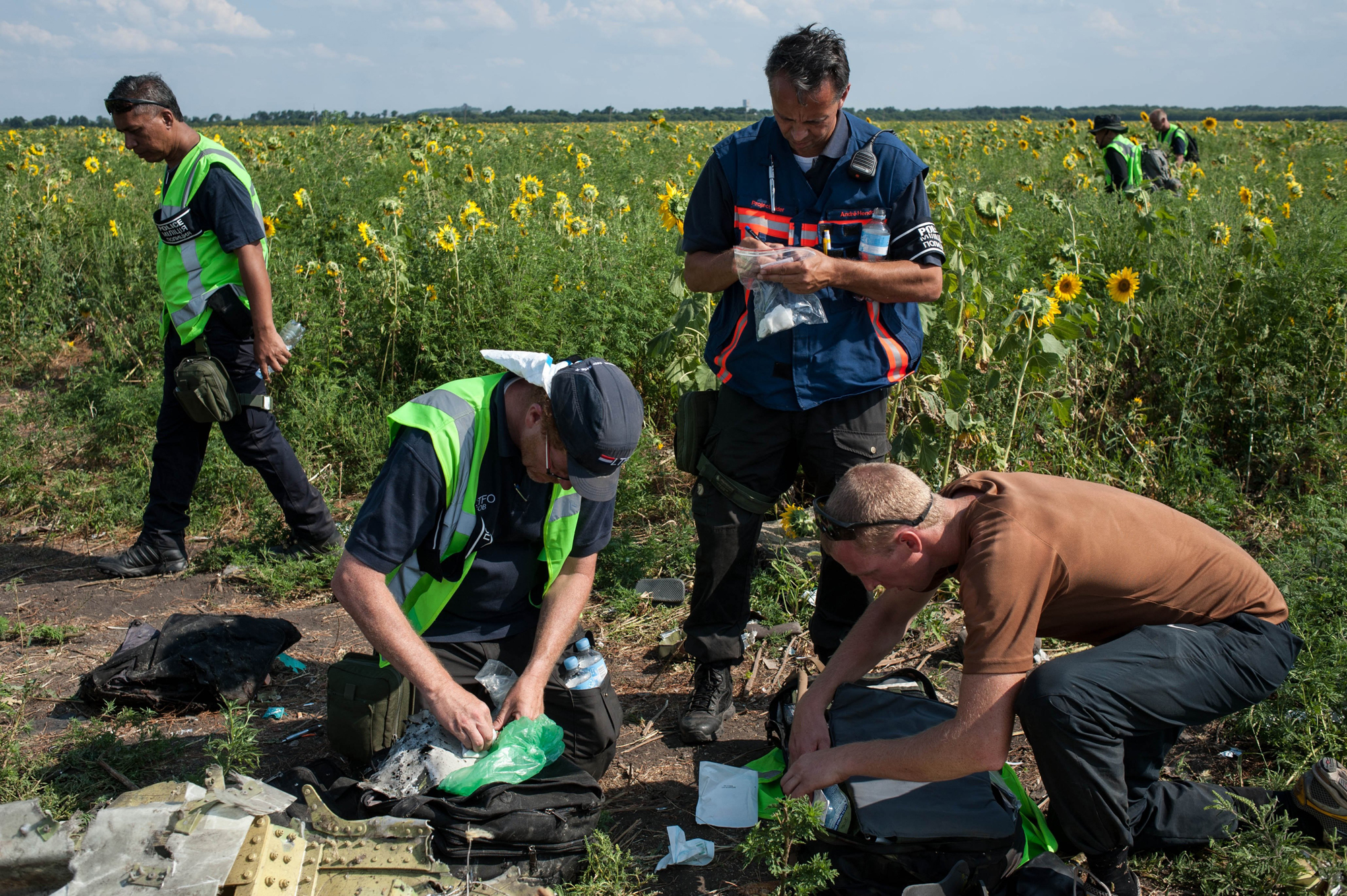 Australian, Malaysian and Dutch investigators examine pieces from the downed Malaysia Airlines Flight 17 plane, near the village of Rossipne, Donetsk region, eastern Ukraine, Aug. 5, 2014.