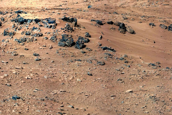 """This patch of windblown sand and dust downhill from a cluster of dark rocks is the """"Rocknest"""" site, which was the location for the first use of the scoop on the arm of Curiosity."""