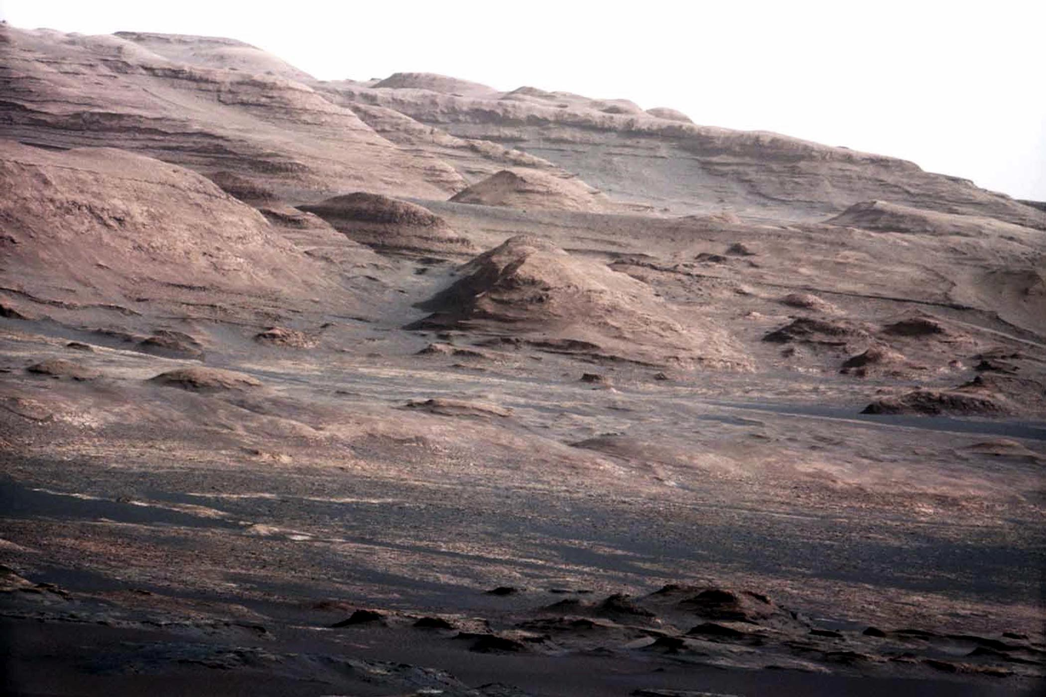 A detailed telephoto view from Curiosity shows Mount Sharp. The rover was expected to reach the 3.4-mile-high peak in February 2013, and the layered surface of the mountain should yield information to scientists on the planet's geological history.