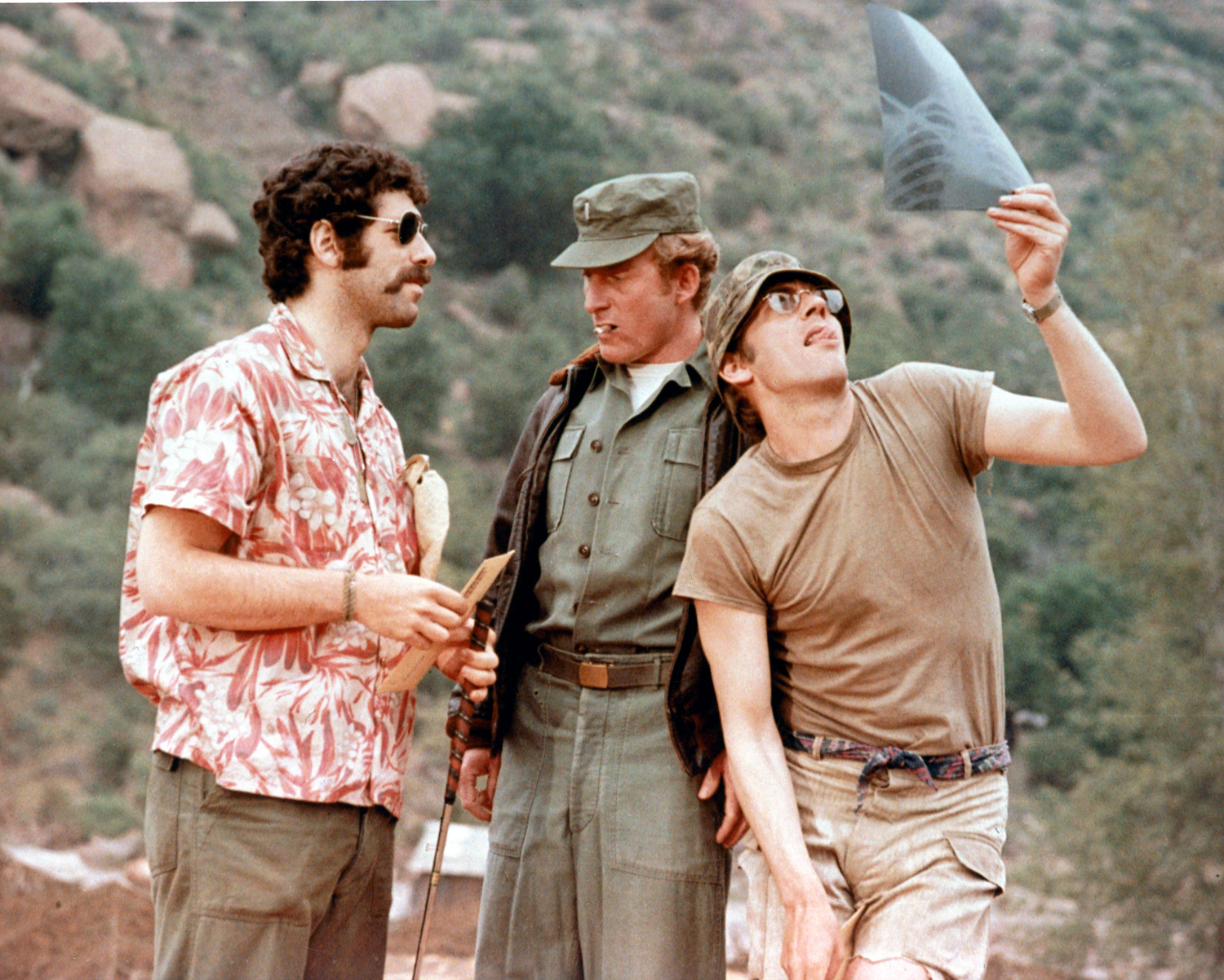 Elliot Gould, left, talking with a uniformed officer smoking a cigarette, and Donald Sutherland, right, examining an x-ray in M*A*S*H.