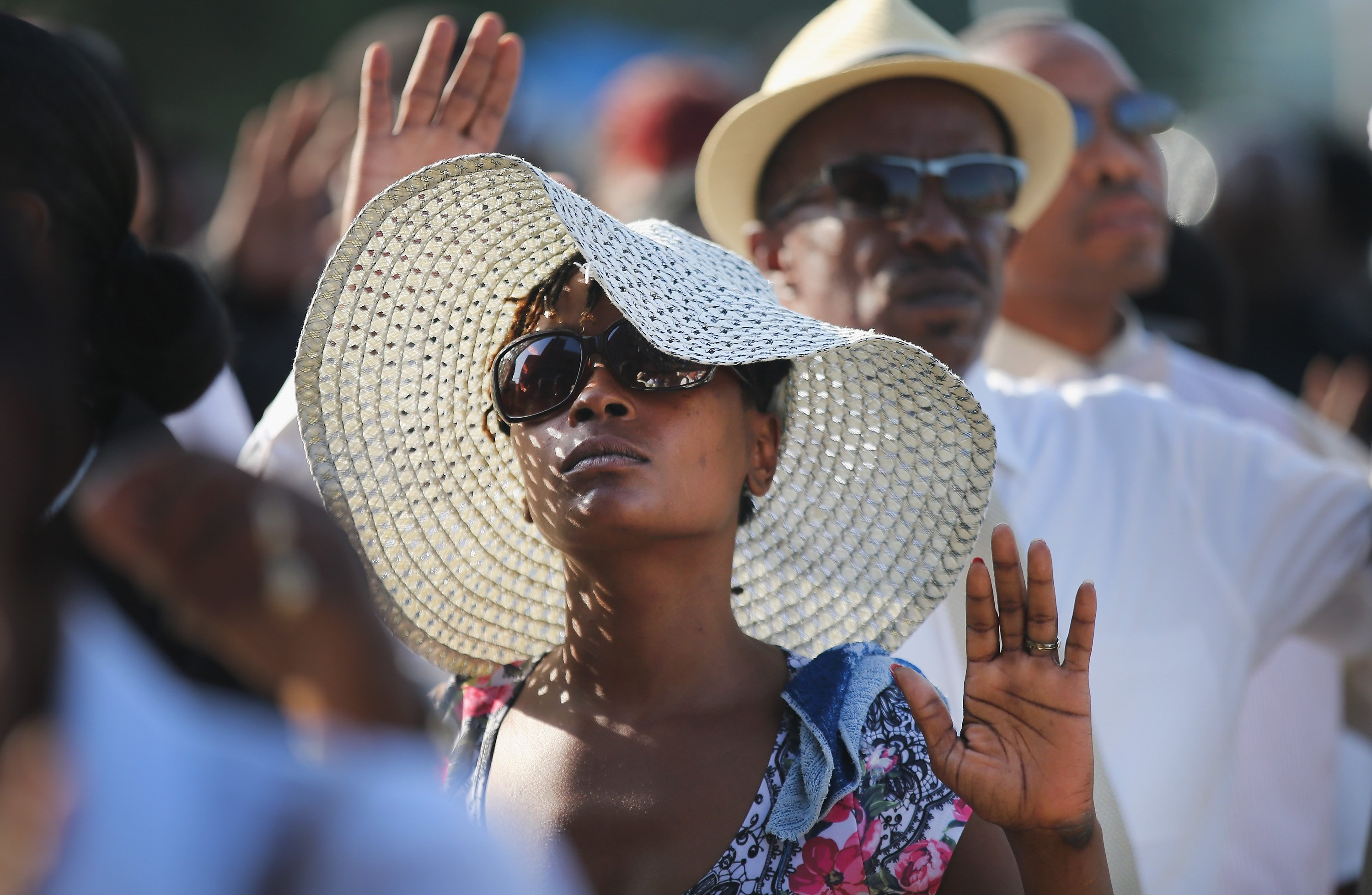 Guests raise their hands as they wait in line to enter the funeral of Michael Brown at the Friendly Temple Missionary Baptist Church in St. Louis on Aug. 25, 2014.