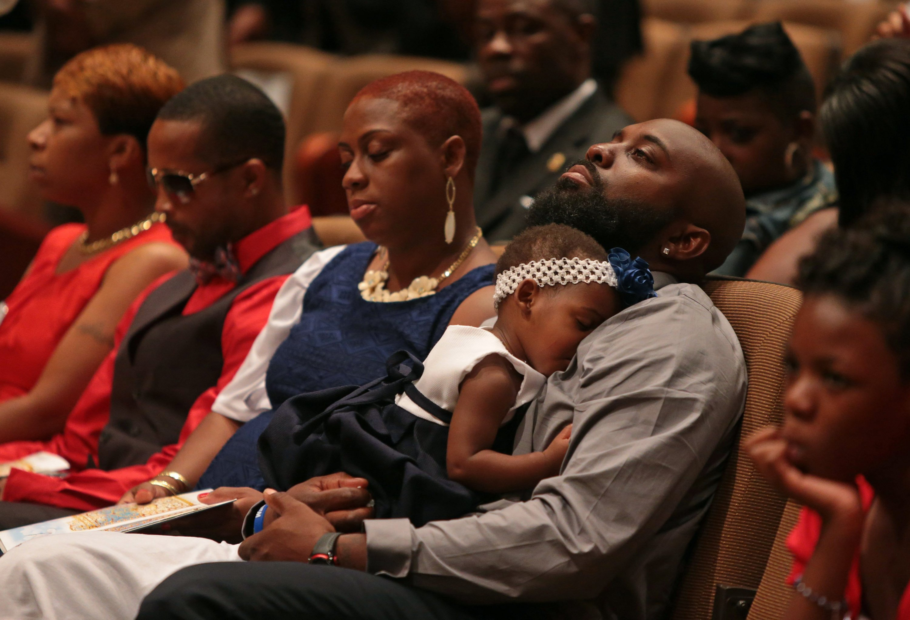 Michael Brown Sr. sits with a child on his lap during the funeral services for his son Michael Brown inside the Friendly Temple Missionary Baptist Church in St. Louis on Aug. 25, 2014.