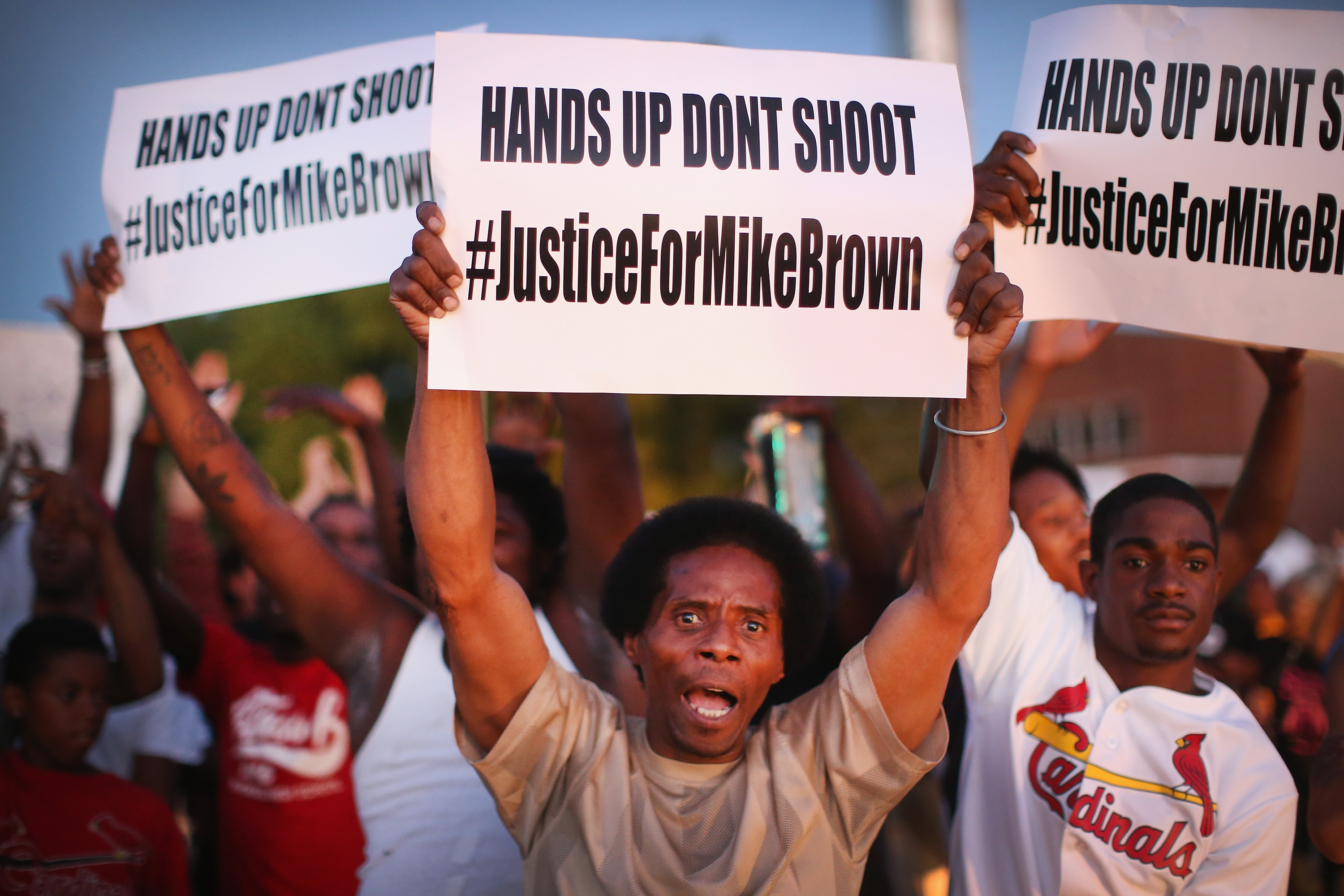 Demonstrators protest the killing of teenager Michael Brown outside Greater St. Marks Family Church, in St. Louis, while his family along with civil rights leader the Rev. Al Sharpton and others met inside to discuss the killing on Aug. 12, 2014