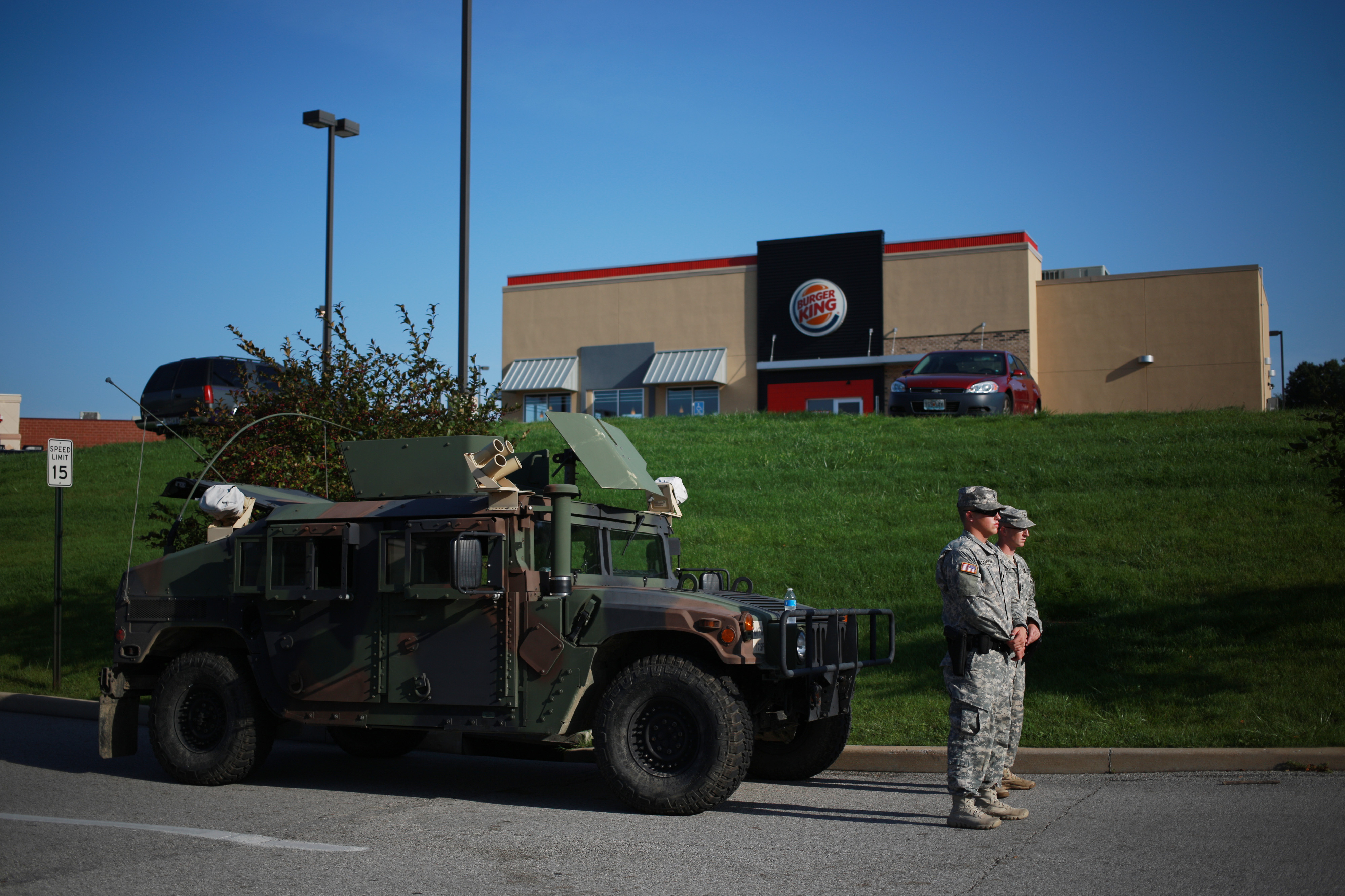 Soldiers from the Missouri National Guard stand in front of their Humvee vehicle outside a Burger King restaurant as they man an entrance to a temporary police command center in Ferguson, Missouri on Aug. 20, 2014.