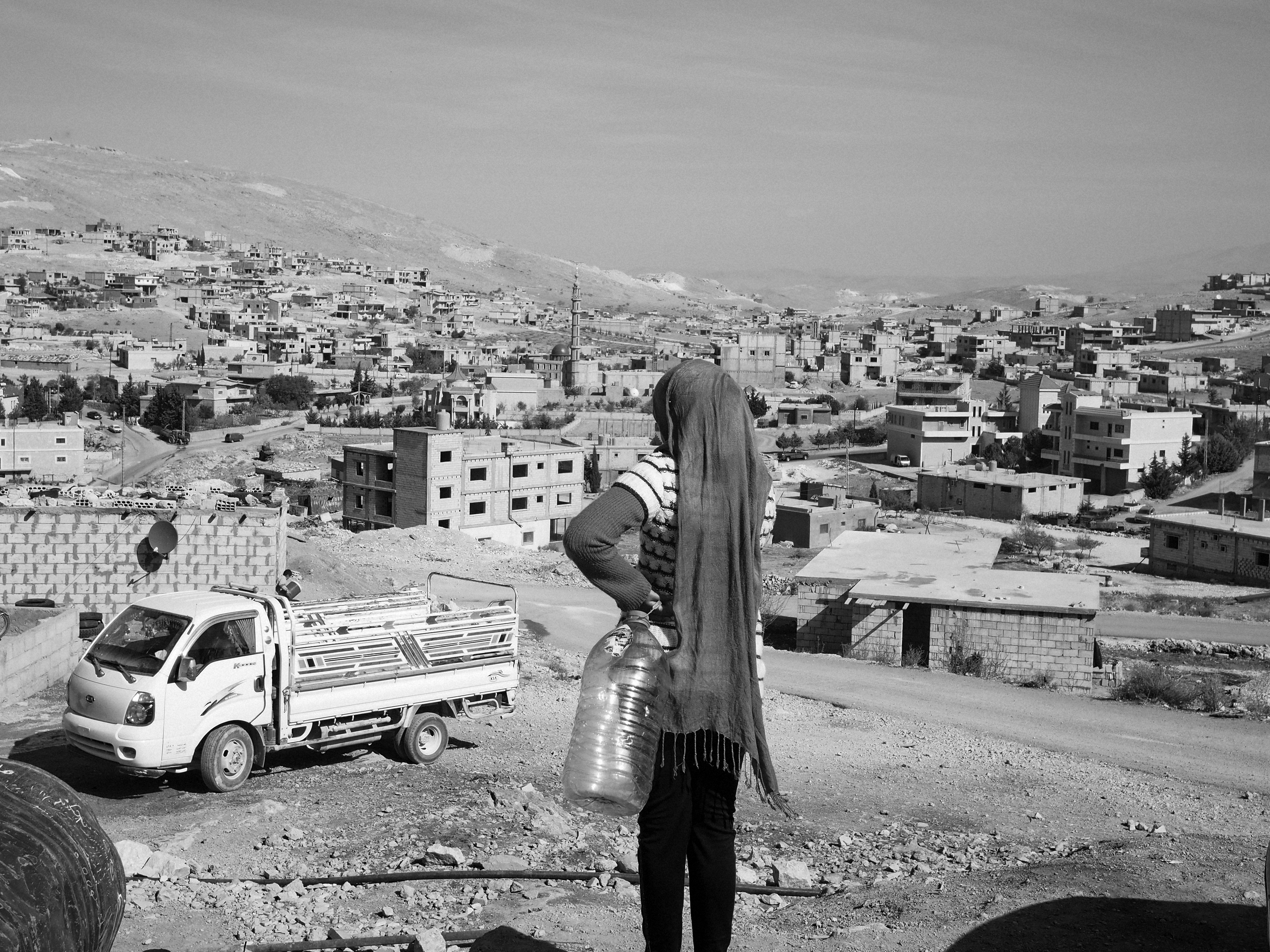 A Syrian refugee on her way to fetch drinking water in the village of Arsal, Lebanon.