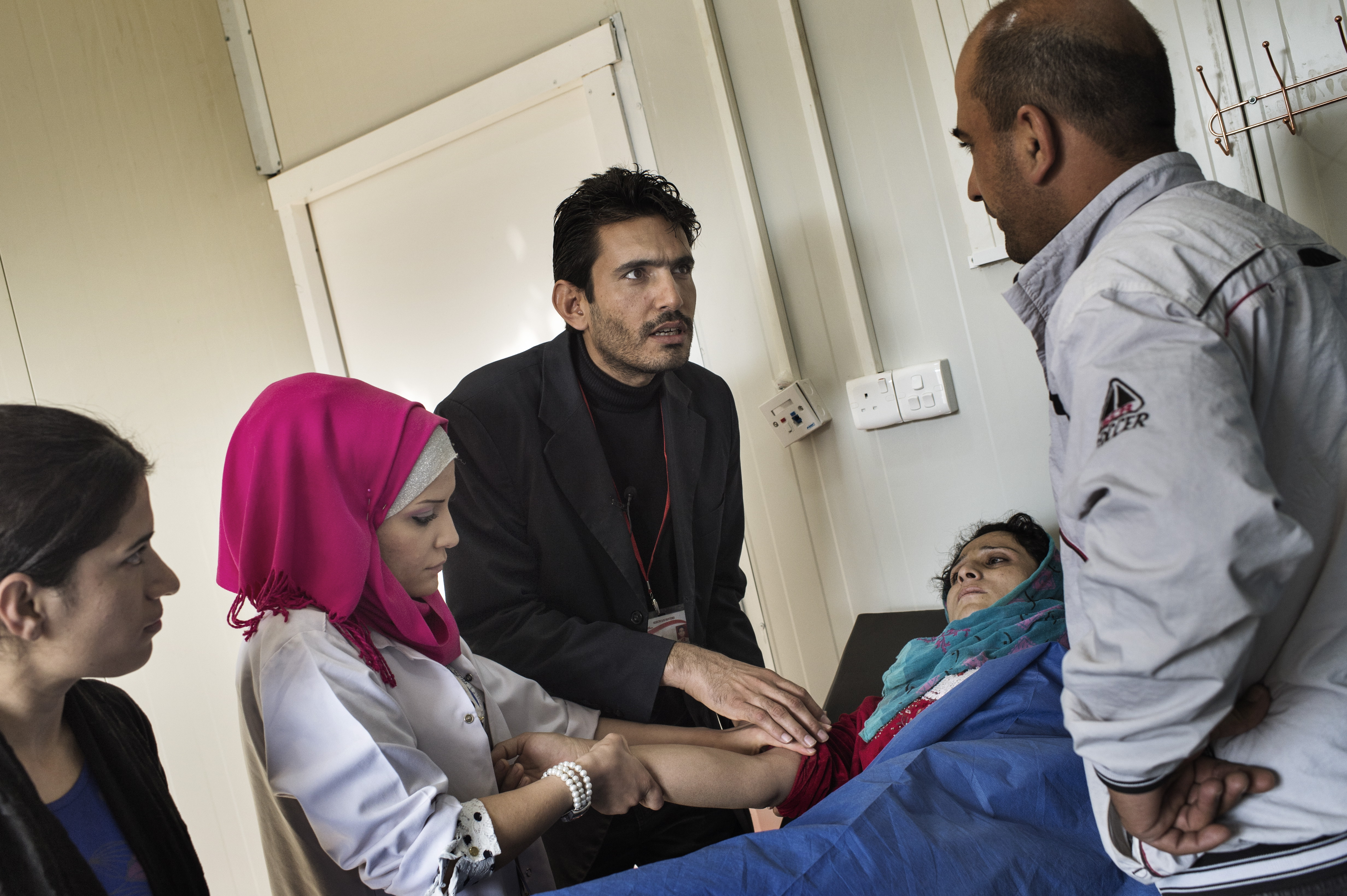 Dr. Mustapha Khalil, medical coordinator at the Doctors Without Borders health clinic in the Domiz refugee camp in northeast Iraq, tends to an ill patient, November 6, 2013.