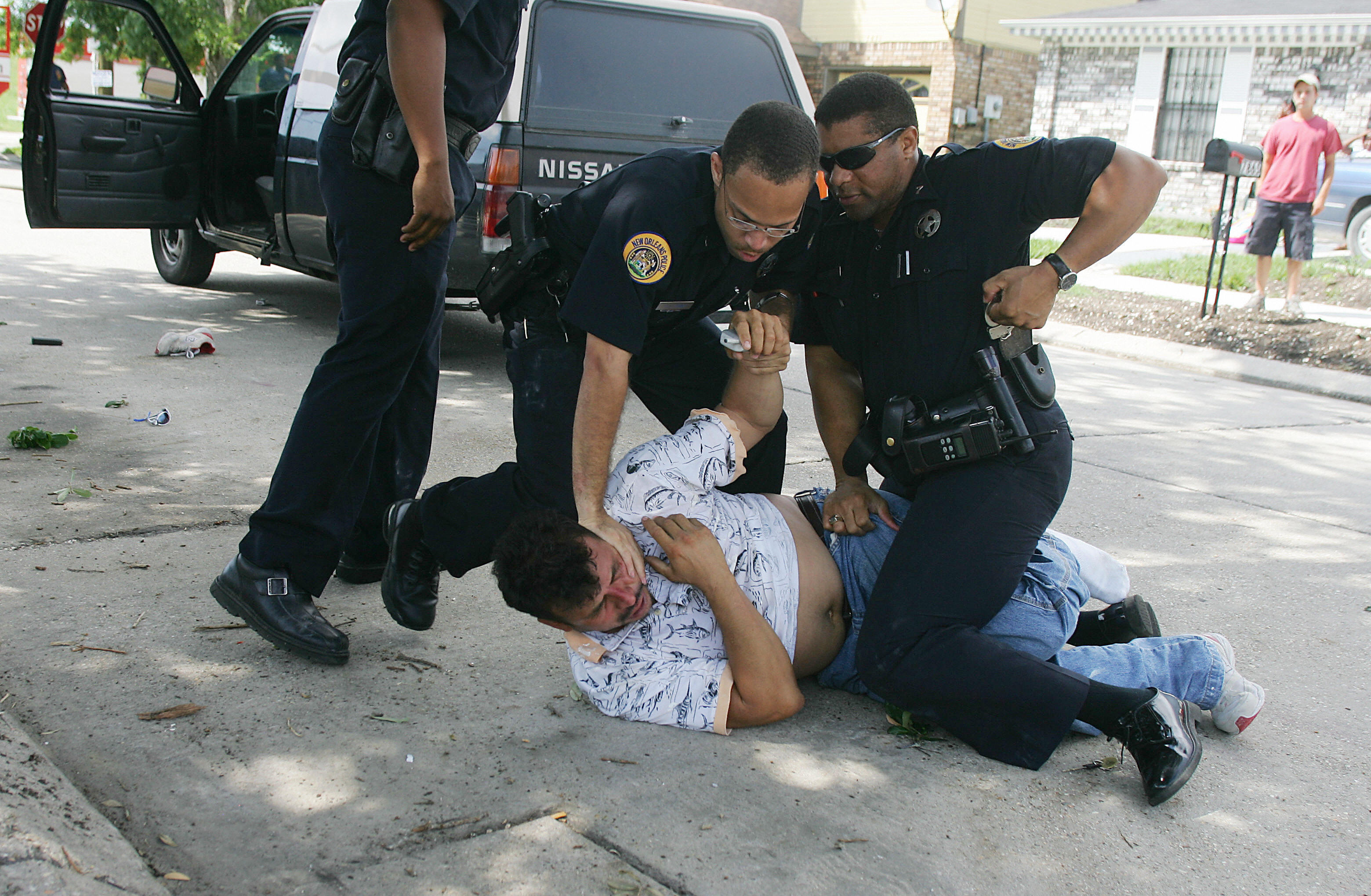 New Orleans Police subdue a man who refused to cooperate when he was asked to step out of his car and who was found to have a knife in the front seat, at the scene of a house fire in New Orleans East on July 6, 2006.