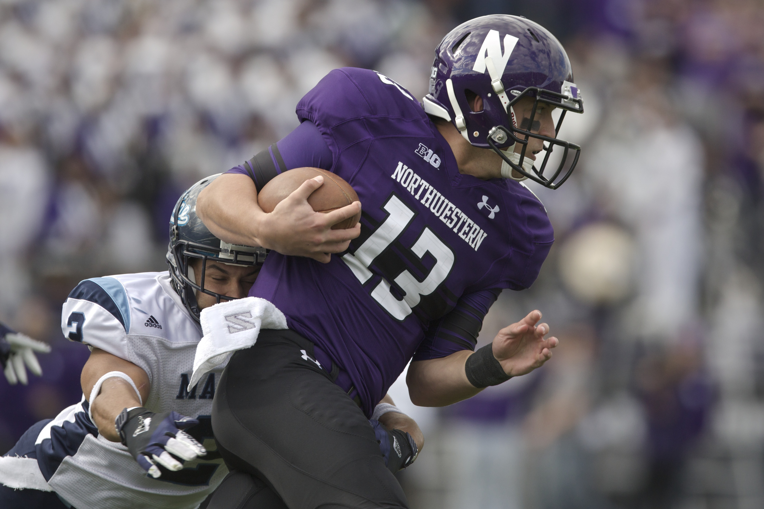 Cabrinni Goncalvesof the Maine Black Bears tackles Trevor Siemianof the Northwestern Wildcats during their college football game at Ryan Field on September 21, 2013 in Evanston, Illinois.
