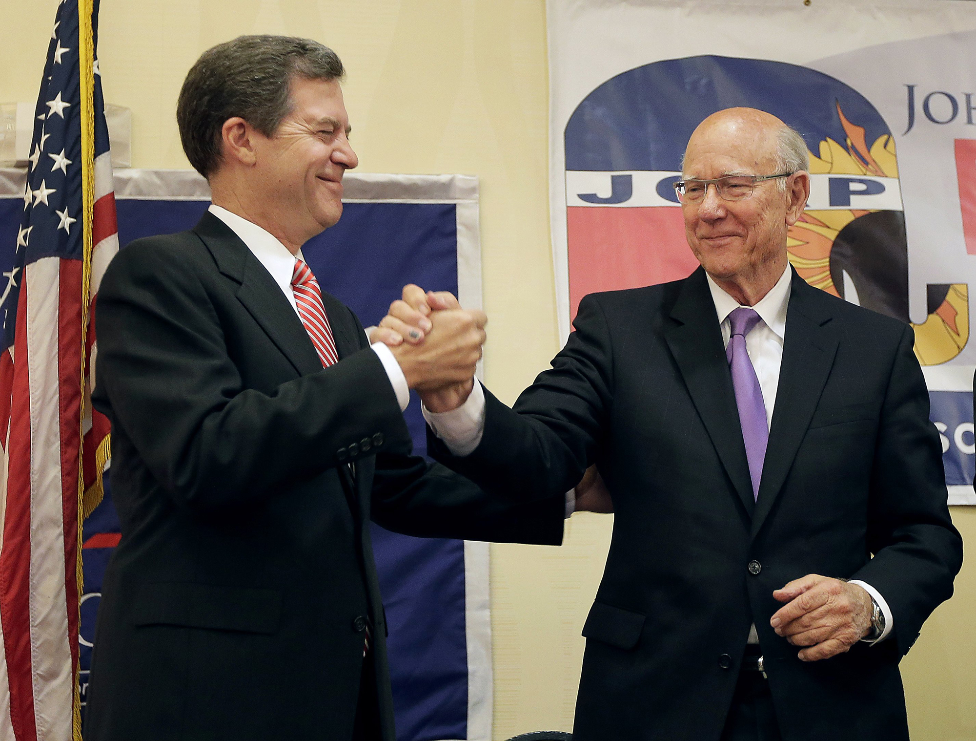Kansas Gov. Sam Brownback, left, and U.S. Sen. Pat Roberts greet each other at Johnson County Republican's election watch party, Aug. 5, 2014, in Overland Park, Kan.