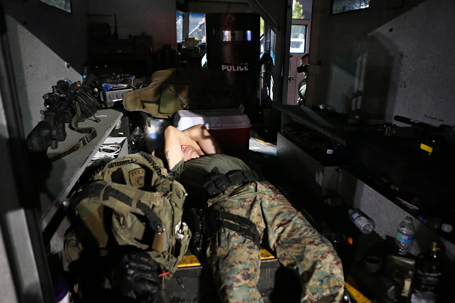 Aug. 19, 2014. A member of the St. Louis County Police tactical team sleeps in the back of the team's armored truck after arriving back at the command post W. Florissant Avenue at about 2.49 a.m.