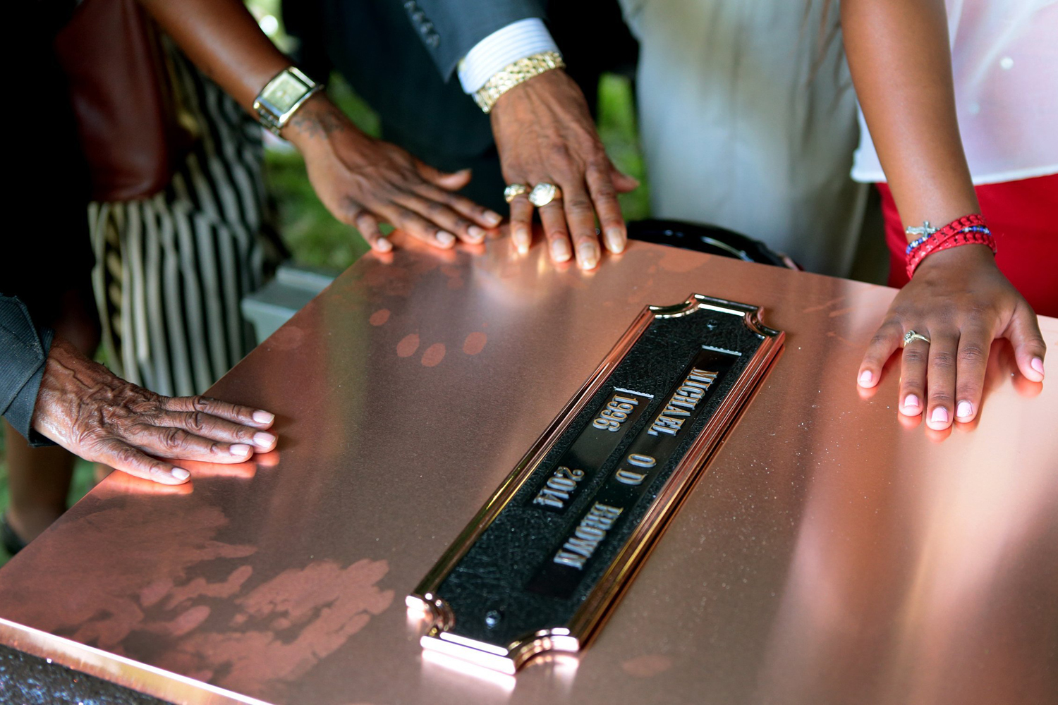 Aug. 25, 2014. Family members touch the copper top of the vault containing the casket of Michael Brown during his burial at St. Peter's Cemetery.