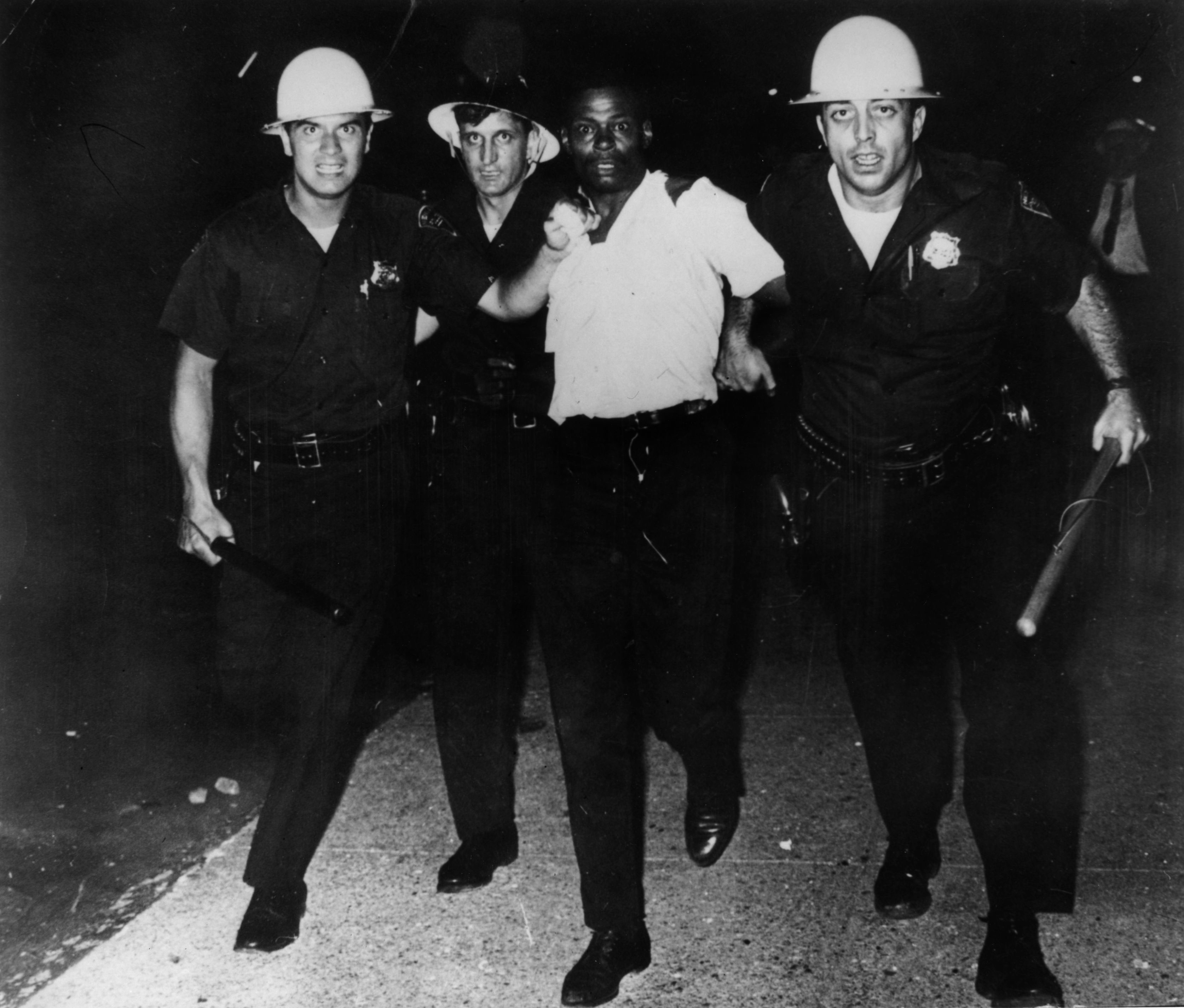 Three policemen taking away a civil rights protester during race riots in Newark, N.J., 1967.